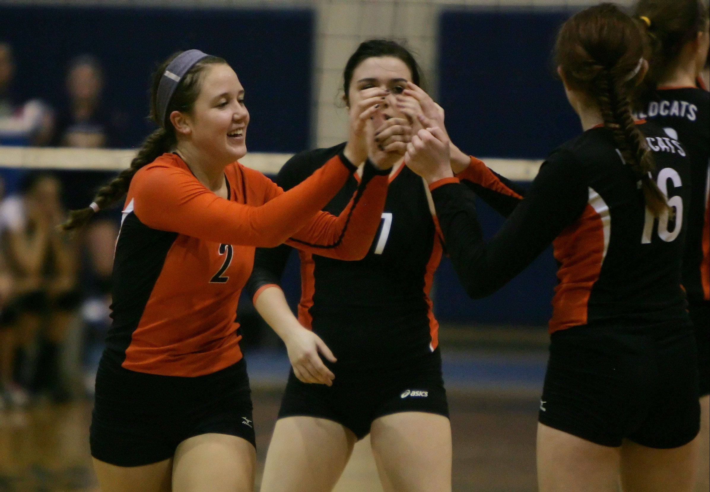 Libertyville's Kristen Webb is congratulated by teammates after winning a point on her serve during regional semifinal play Tuesday between the Wildcats and Mundelein at Lake Zurich.