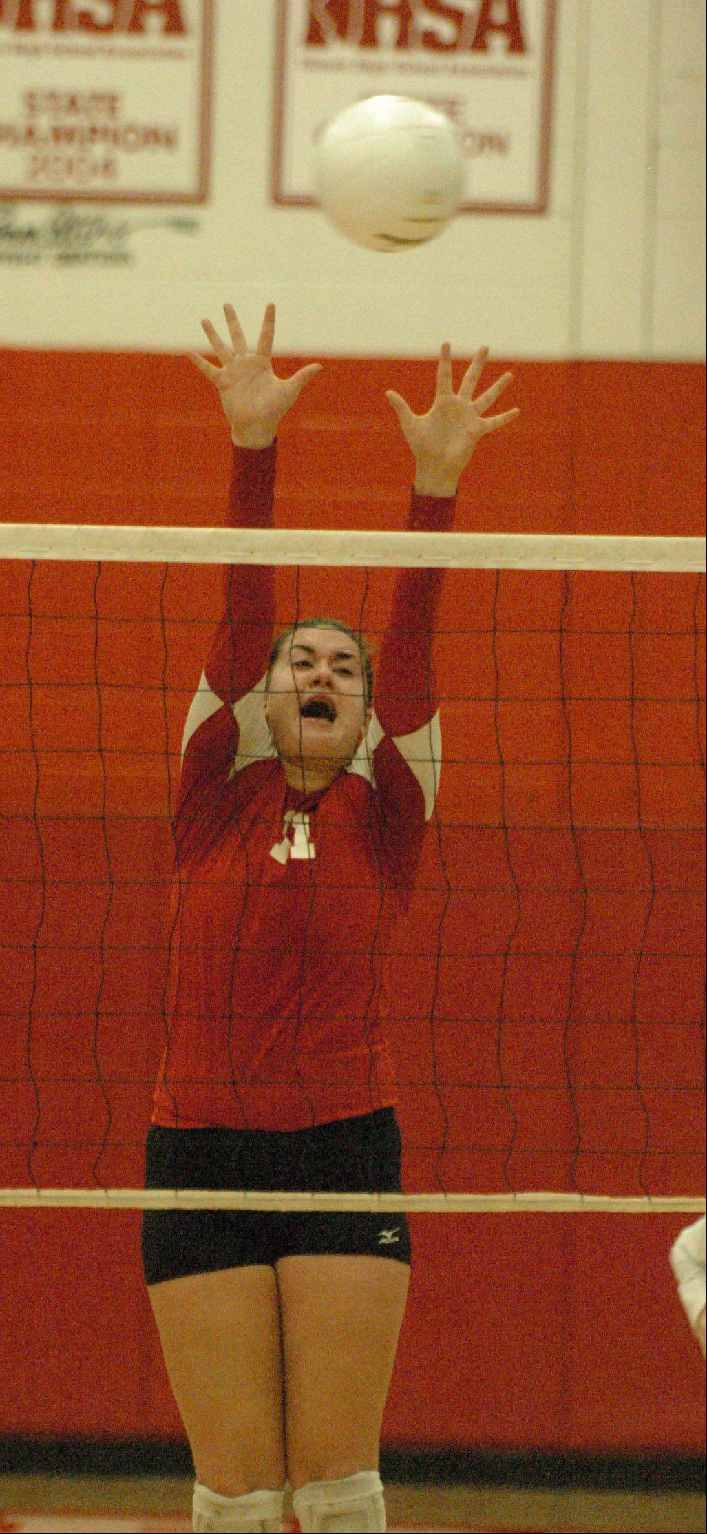 Maddie Siambekos of Naperville Central blocks a shot during the Naperville Central vs. Naperville North girls volleyball game at Naperville Central Tuesday.