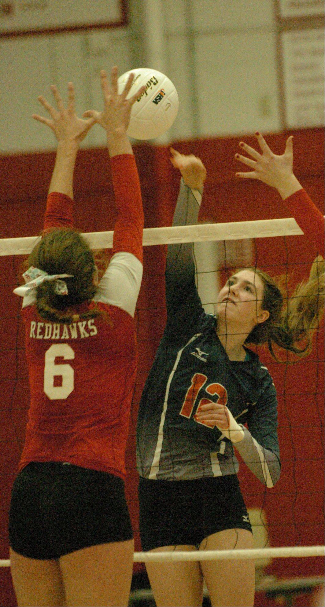 Alysia Baznik of Naperville Central goes up for a block while Becky Welch of Naperville Noth hits it. This took place during the Naperville Central vs. Naperville North girls volleyball at Naperville Central Tuesday.