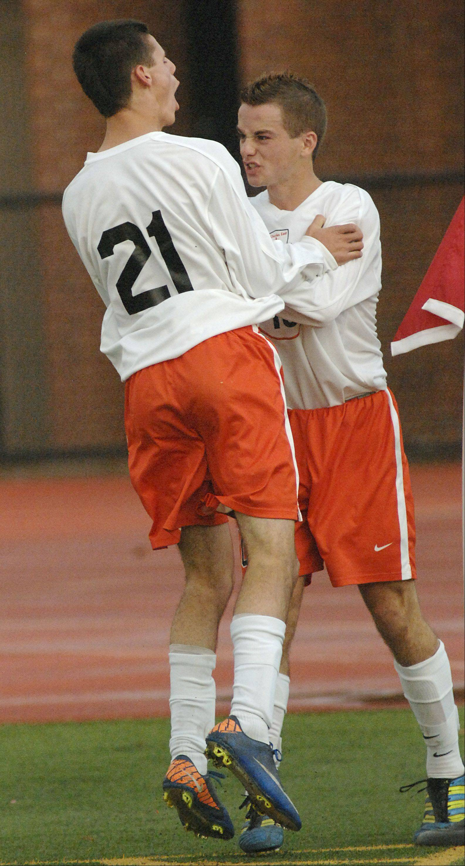 St. Charles East's Daniel DiLeonardi (21) congratulates T.C. Hull on his goal in the first half on Tuesday, October 23.