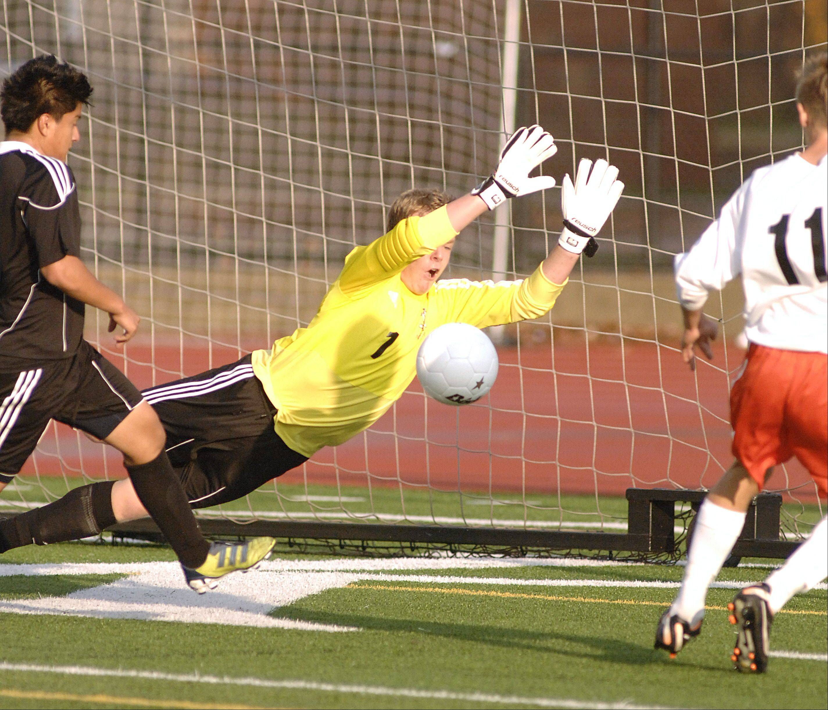 Streamwood's Phil Lewy dives in an attempt to block a goal kick by St. Charles East's Eric Dietrich in the first half on Tuesday, October 23.