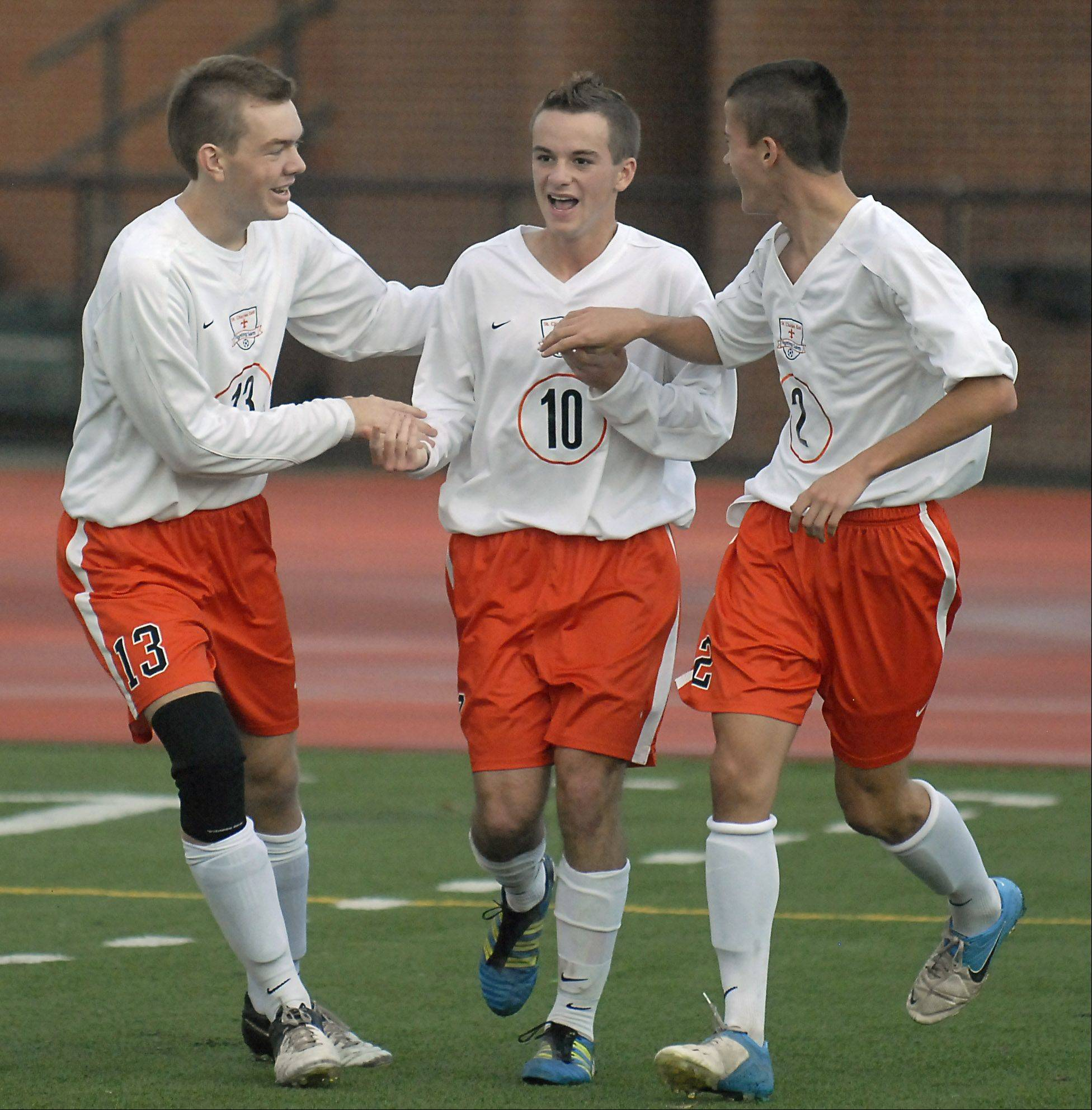 St. Charles East's T.C. Hull (10) gets congrats from teammates Elliot Welter (13) and Cooper Macek in the first half on Tuesday, October 23.