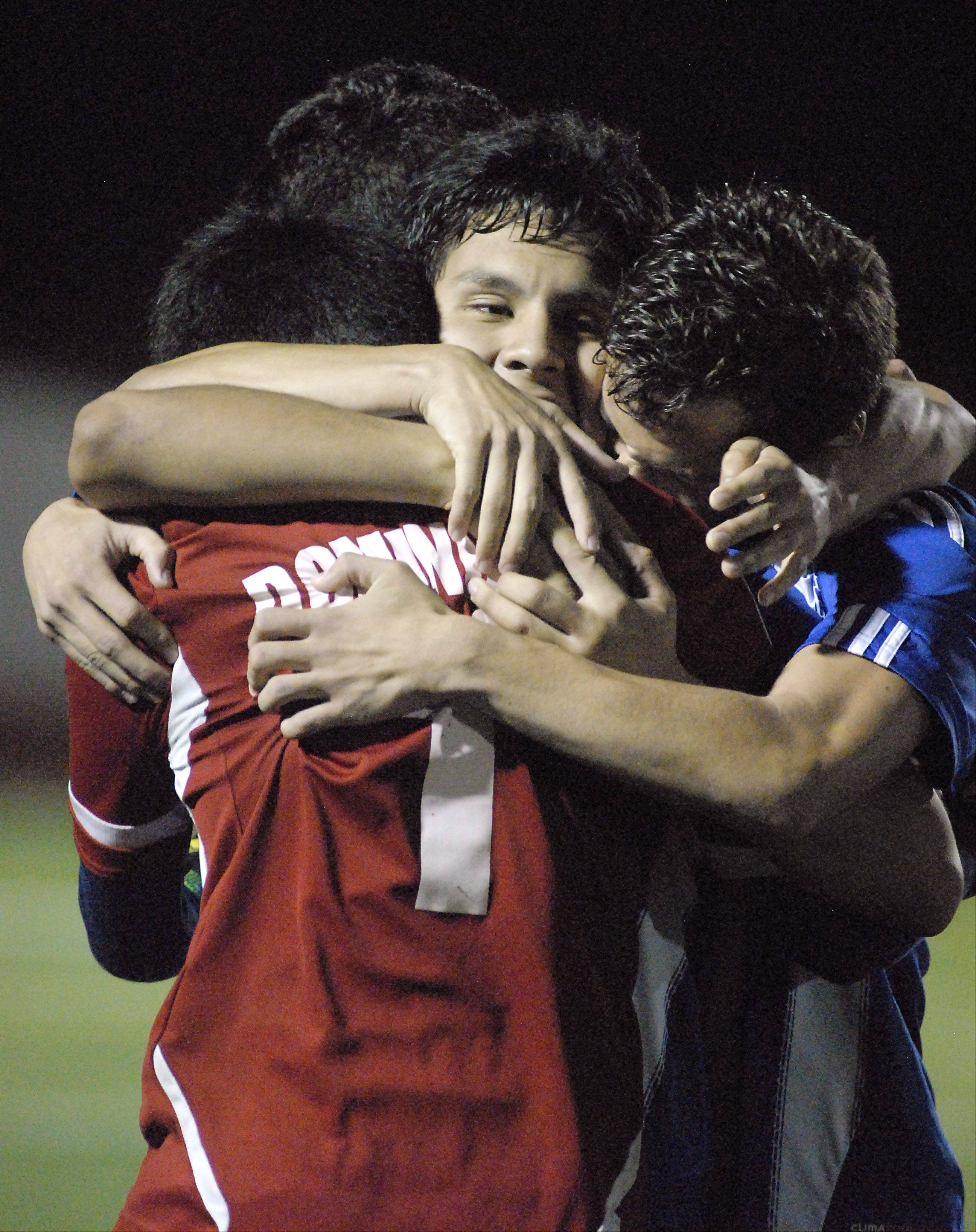 Larkin's Freddy Alvarez, facing, is swarmed by goalie Aldair Dominguez and fellow teammates after scoring the sudden death goal over South Elgin after two overtimes on Tuesday, October 23.