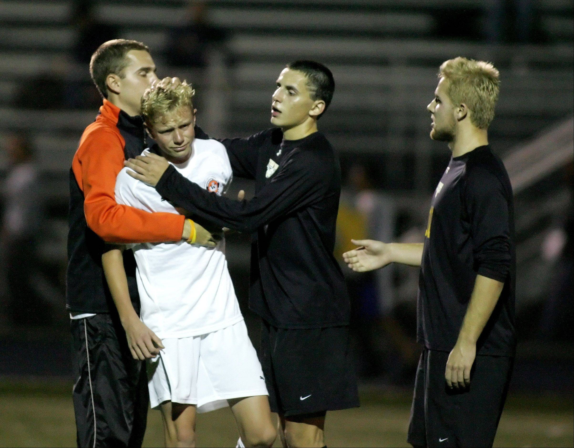 Franco Cattani and Jake Goehring, on the right, of Metea Valley, help console Patrick Nielsen of Wheaton Warrenville South after Metea won 1-0 in boys Class 3A sectional soccer in West Chicago.