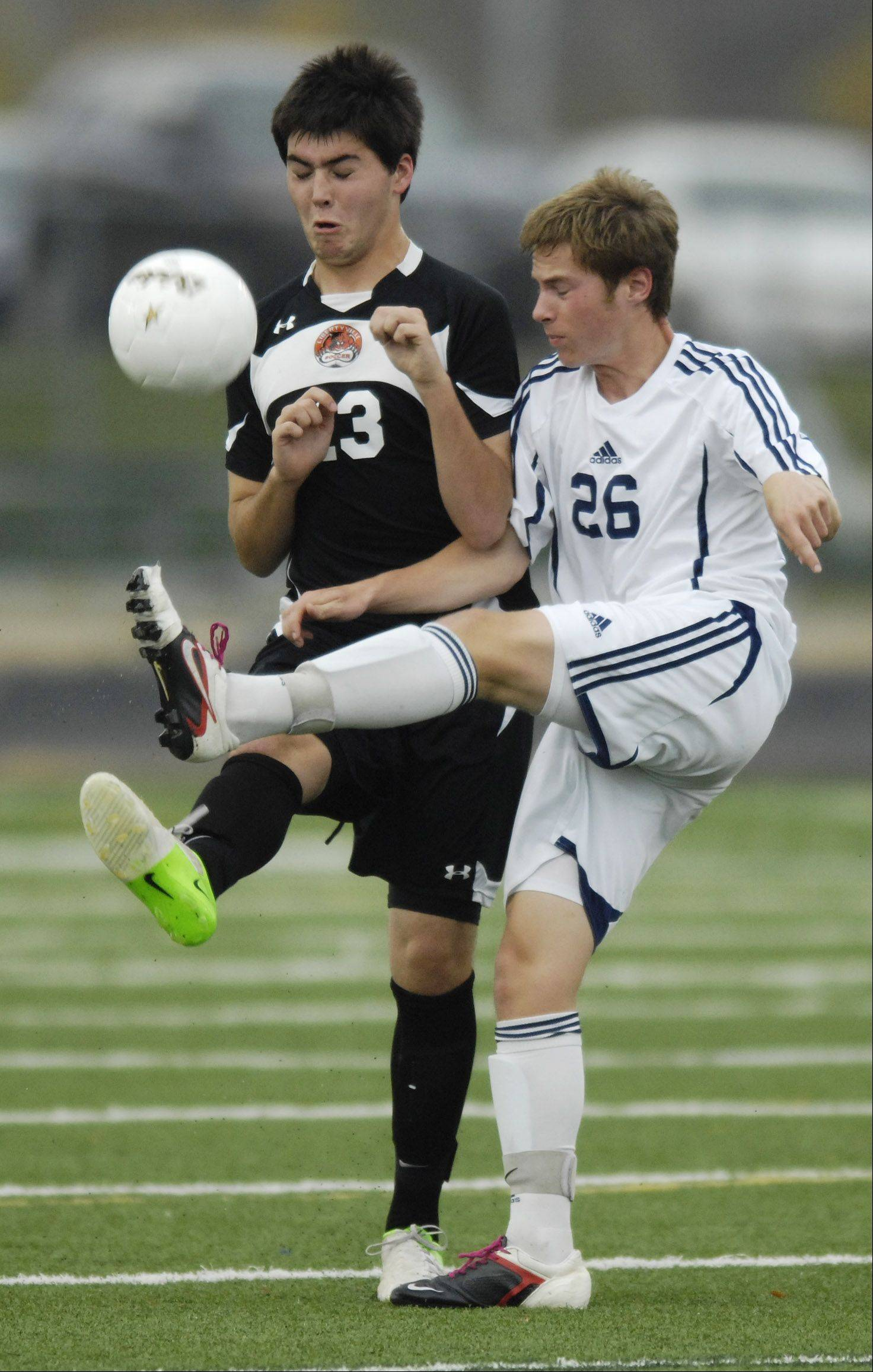 Prospect's Steven Mutzabaugh, right, gets to the ball ahead of Libertyville's Phillip Williams during Tuesday's sectional semifinal at Conant.