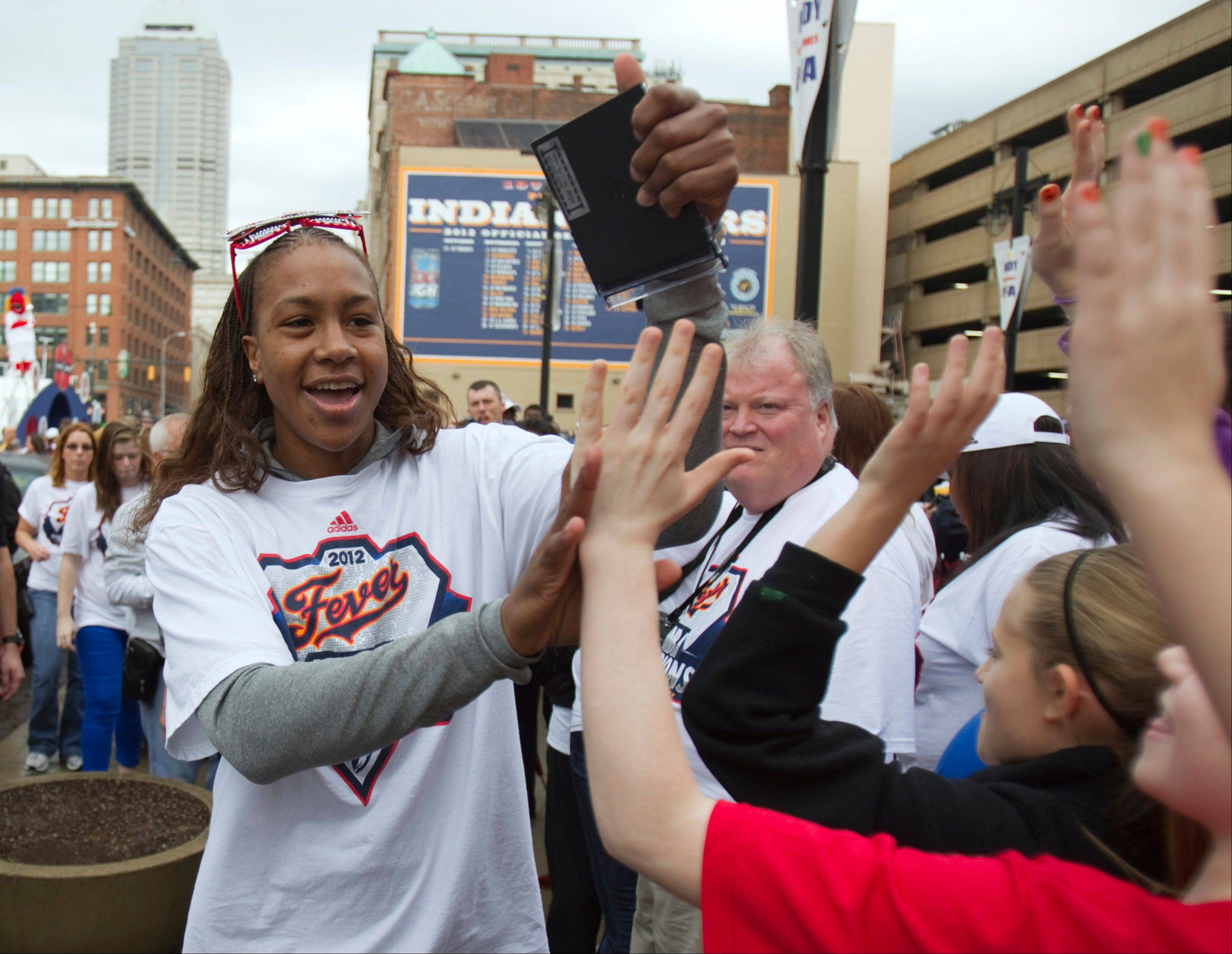 Indiana Fever's Tamika Catchings, MVP of the WNBA Finals, celebrates with fans at Bankers Life Fieldhouse on Tuesday. The team and several thousand fans moved their party indoors to the field house as morning rain scrapped plans for a parade. The Fever wrapped up the title Sunday night, beating the Minnesota Lynx three games to one.