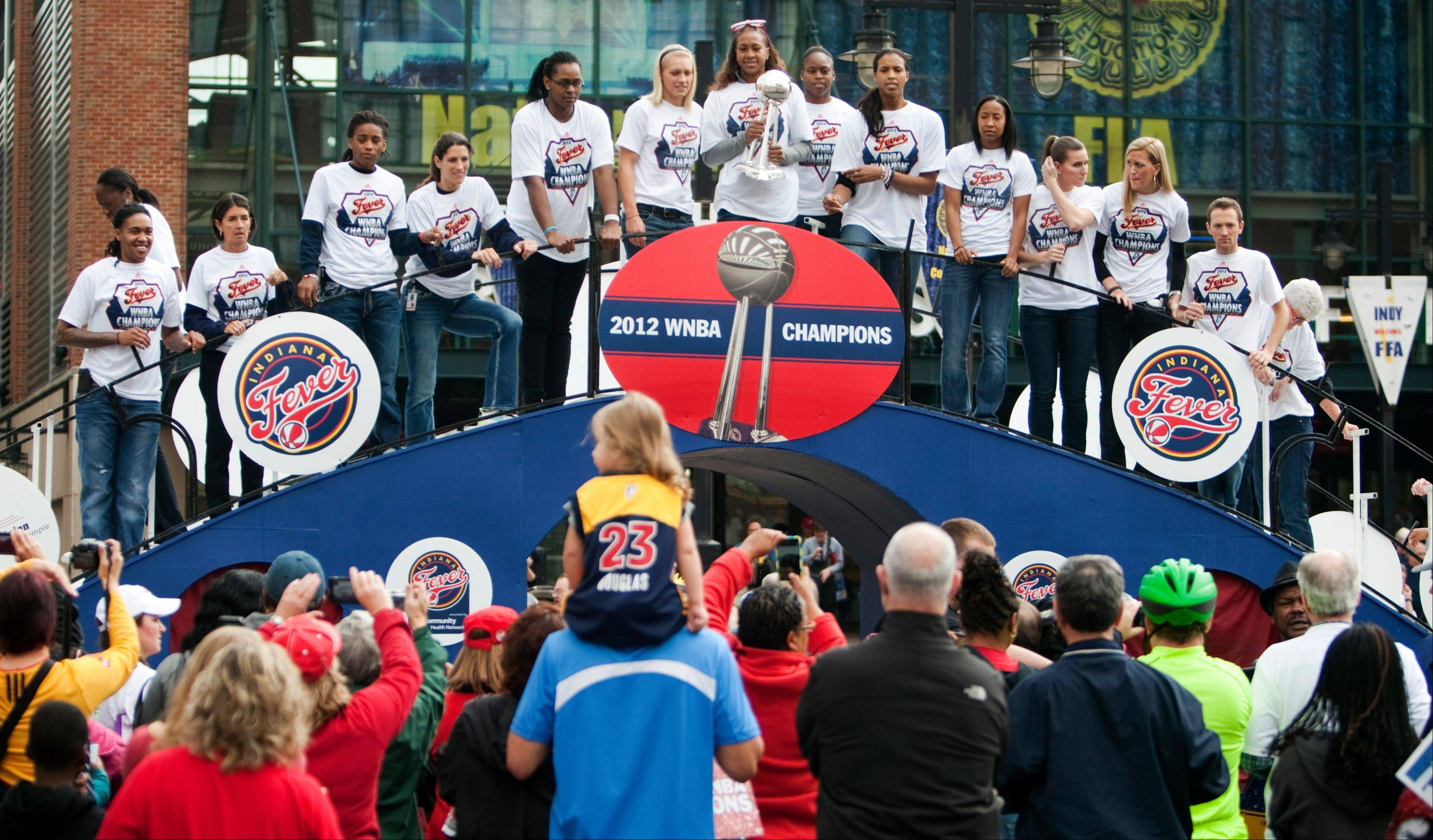 Indiana Fever forward Tamika Catchings, center, holds the trophy atop a float with other members of the team during a celebration for their WNBA basketball championship at Bankers Life Fieldhouse in Indianapolis. The team and several thousand fans moved their party indoors Tuesday as morning rain scrapped plans for a parade.