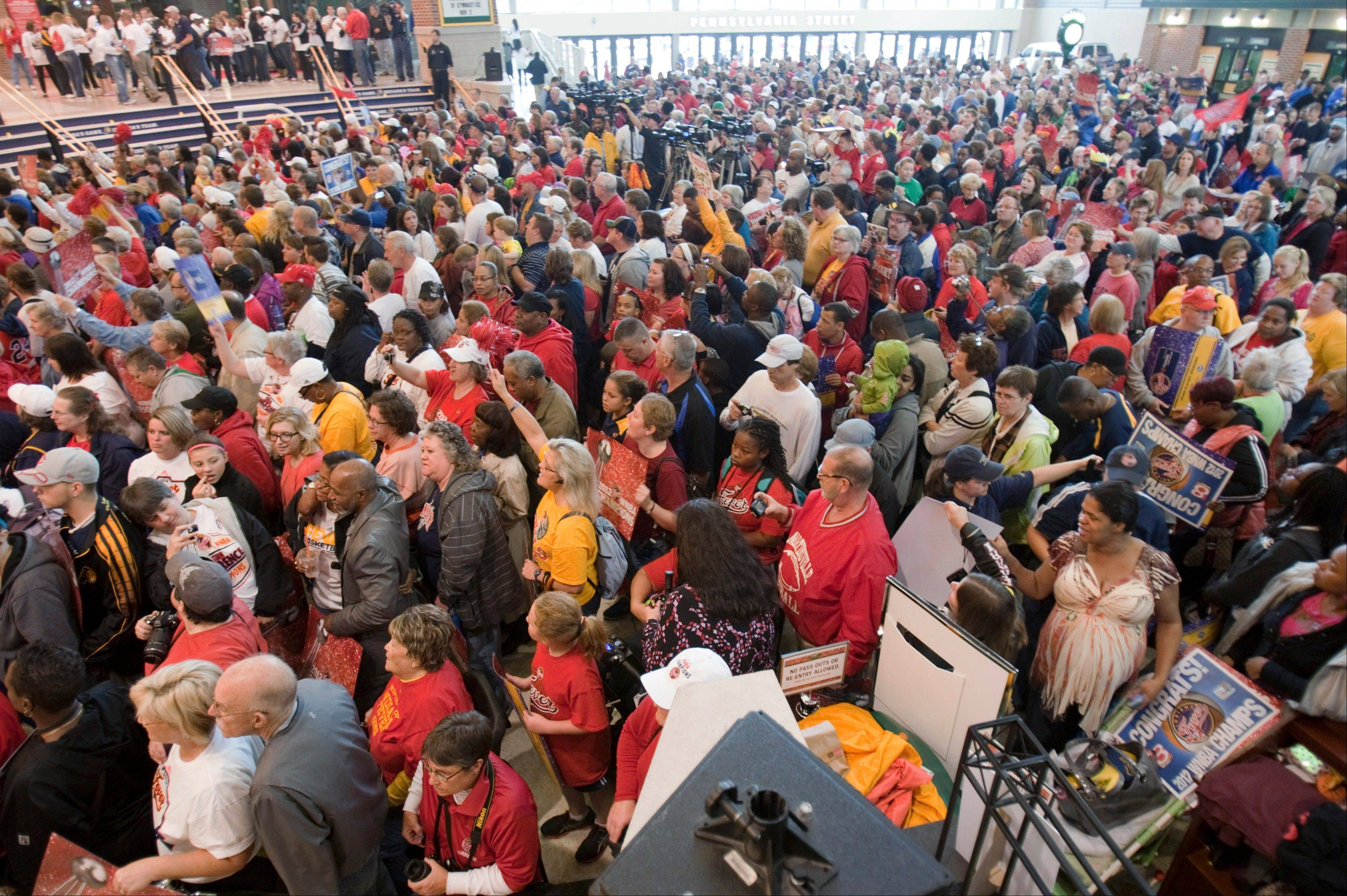 Fans cheer and watch during a celebration for the WNBA-champion Indiana Fever at Bankers Life Fieldhouse on Tuesday in Indianapolis. The team and several thousand fans moved their party indoors as morning rain scrapped plans for a parade.
