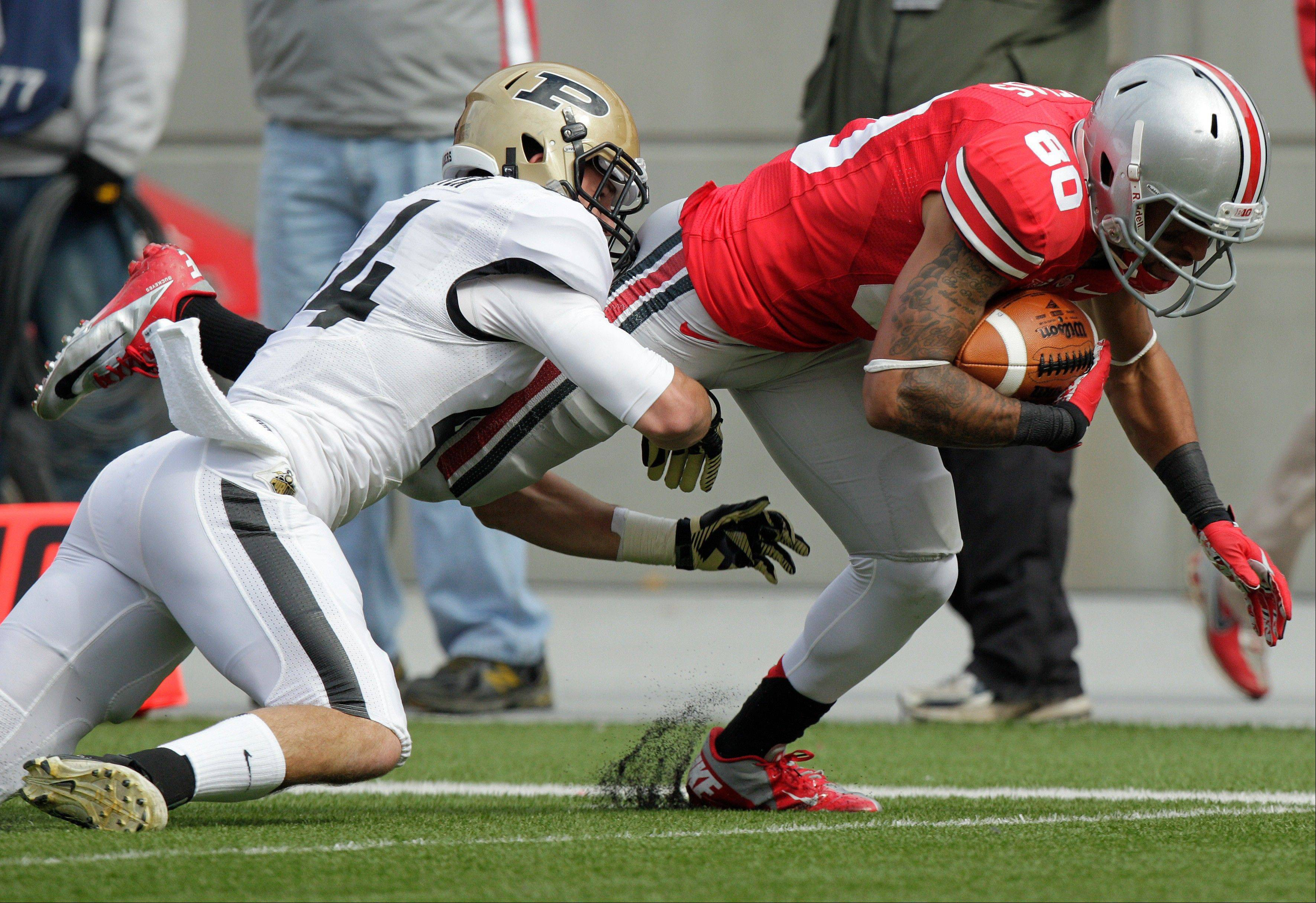 Ohio State wide receiver Chris Fields, right, is tackled by Purdue safety Landon Feichter Saturday during the third quarter. Ohio State and Penn State are both unbeaten in conference play, and they're playing each other this weekend. But thanks to sanctions, neither can compete for the league championship or go to a bowl.