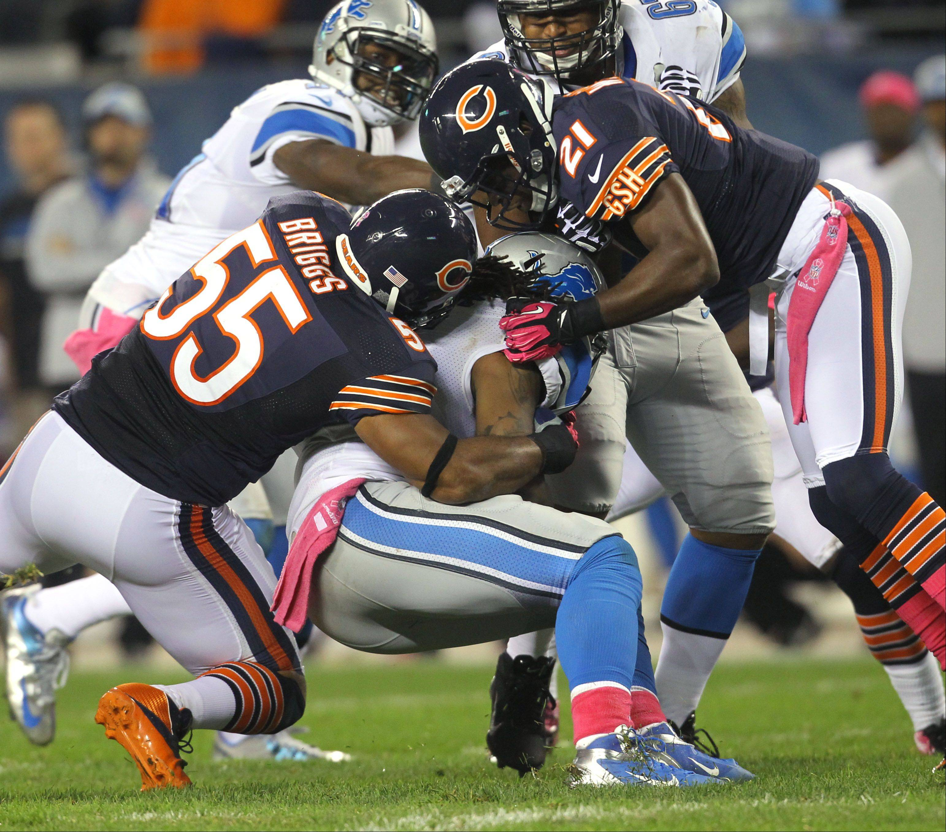 Chicago Bears outside linebacker Lance Briggs and Chicago Bears strong safety Major Wright wrap up Detroit Lions running back Joique Bell.