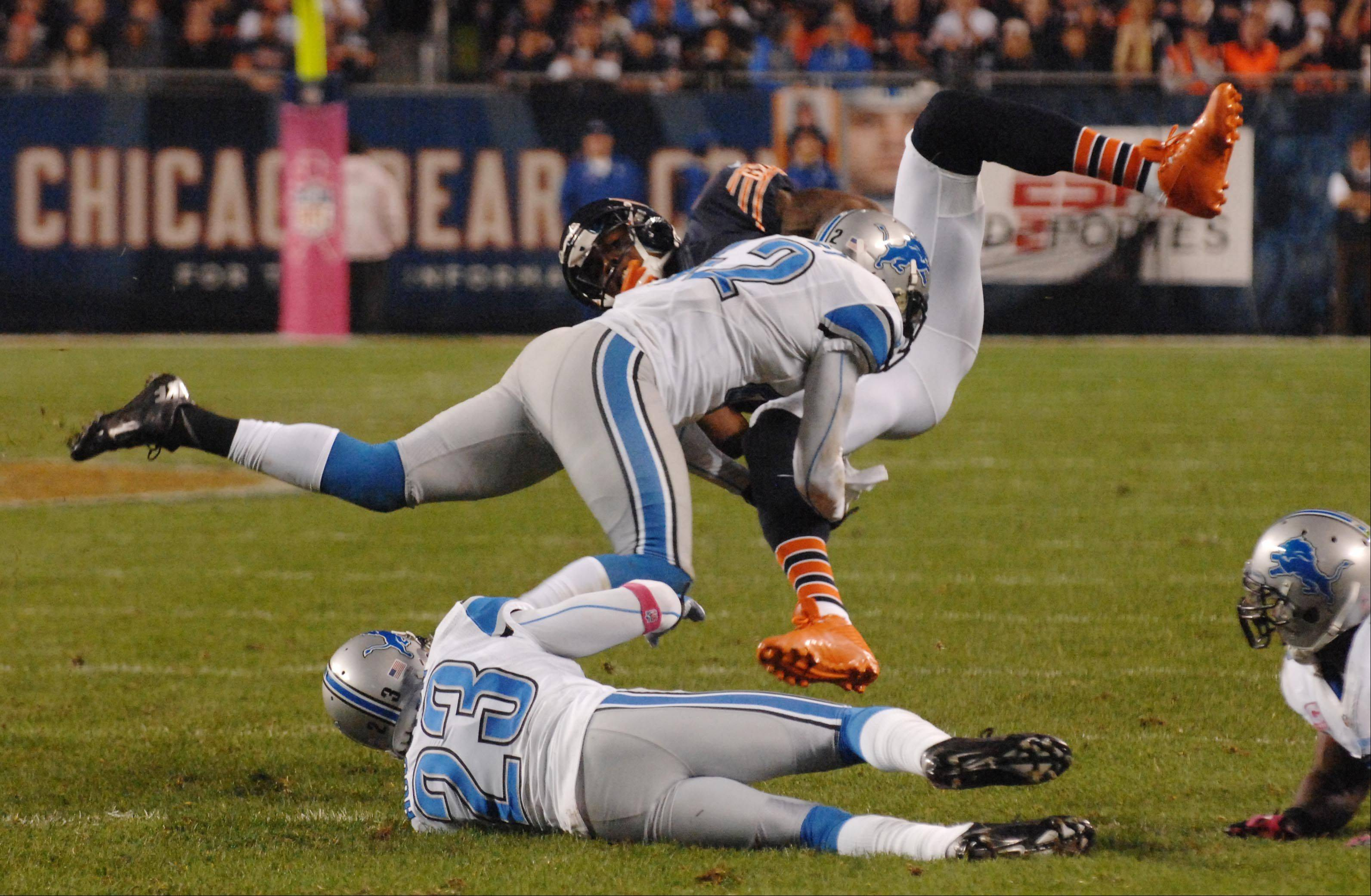 Chicago Bears wide receiver Brandon Marshall is stopped by Detroit Lions outside linebacker Justin Durant and cornerback Chris Houston after an 18-yard catch for a first down.