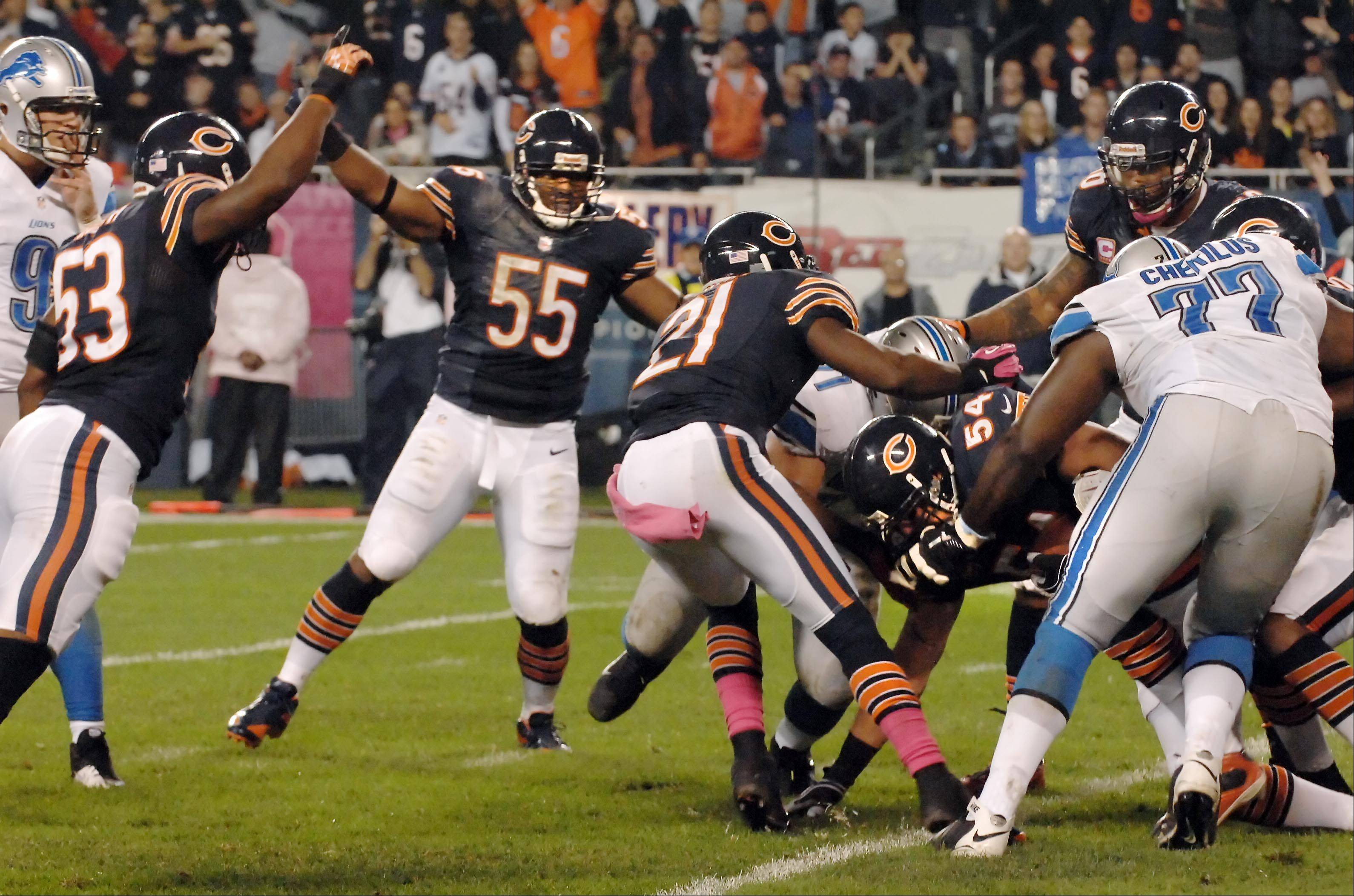 Chicago Bears middle linebacker Brian Urlacher scrambles out of the crowd with a fumble recovery at the goal line as teammates Nick Roach and Lance Briggs celebrate late in the game.