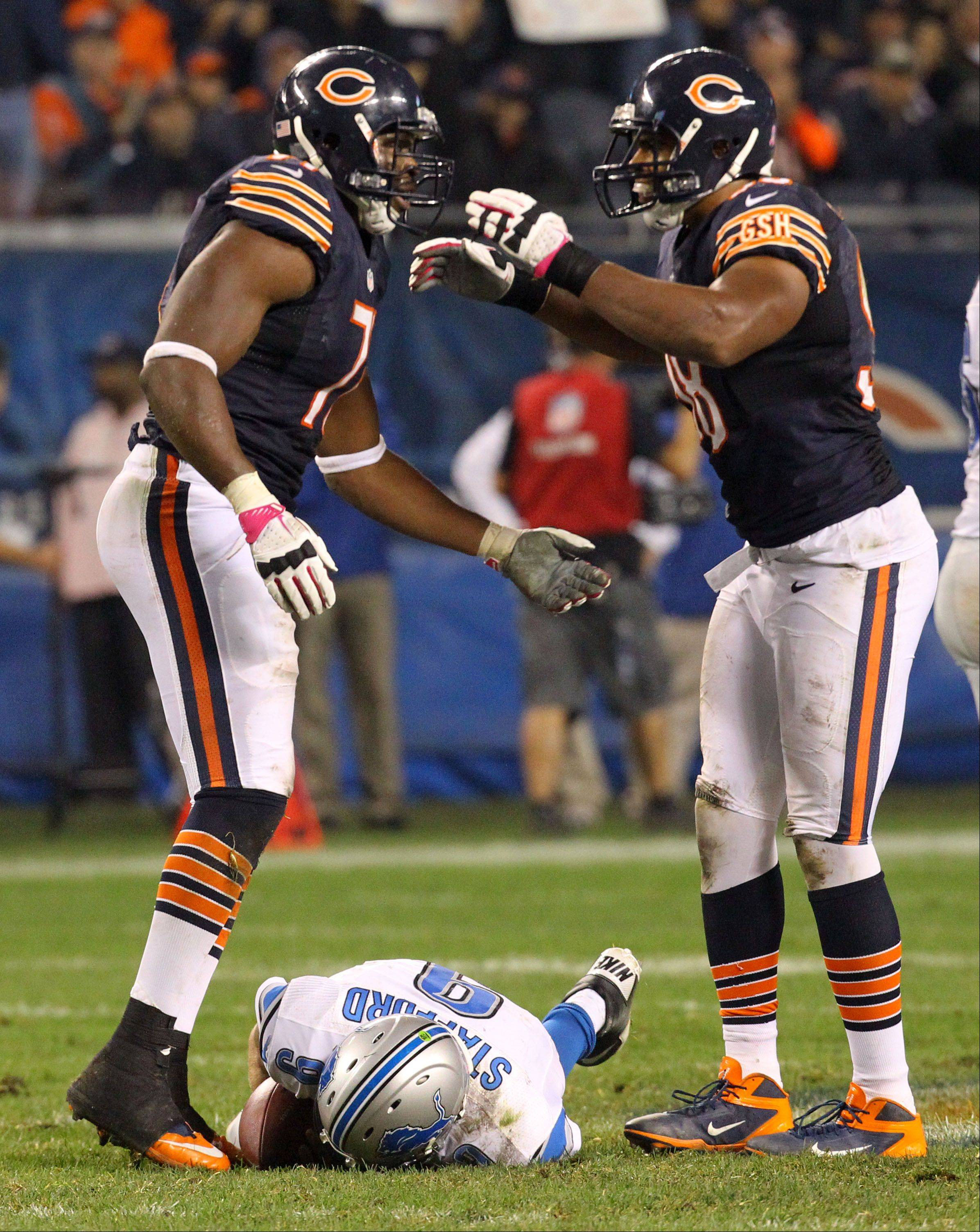 Chicago Bears defensive end Israel Idonije and Chicago Bears defensive end Corey Wootton celebrate after sacking Detroit Lions quarterback Matthew Stafford.