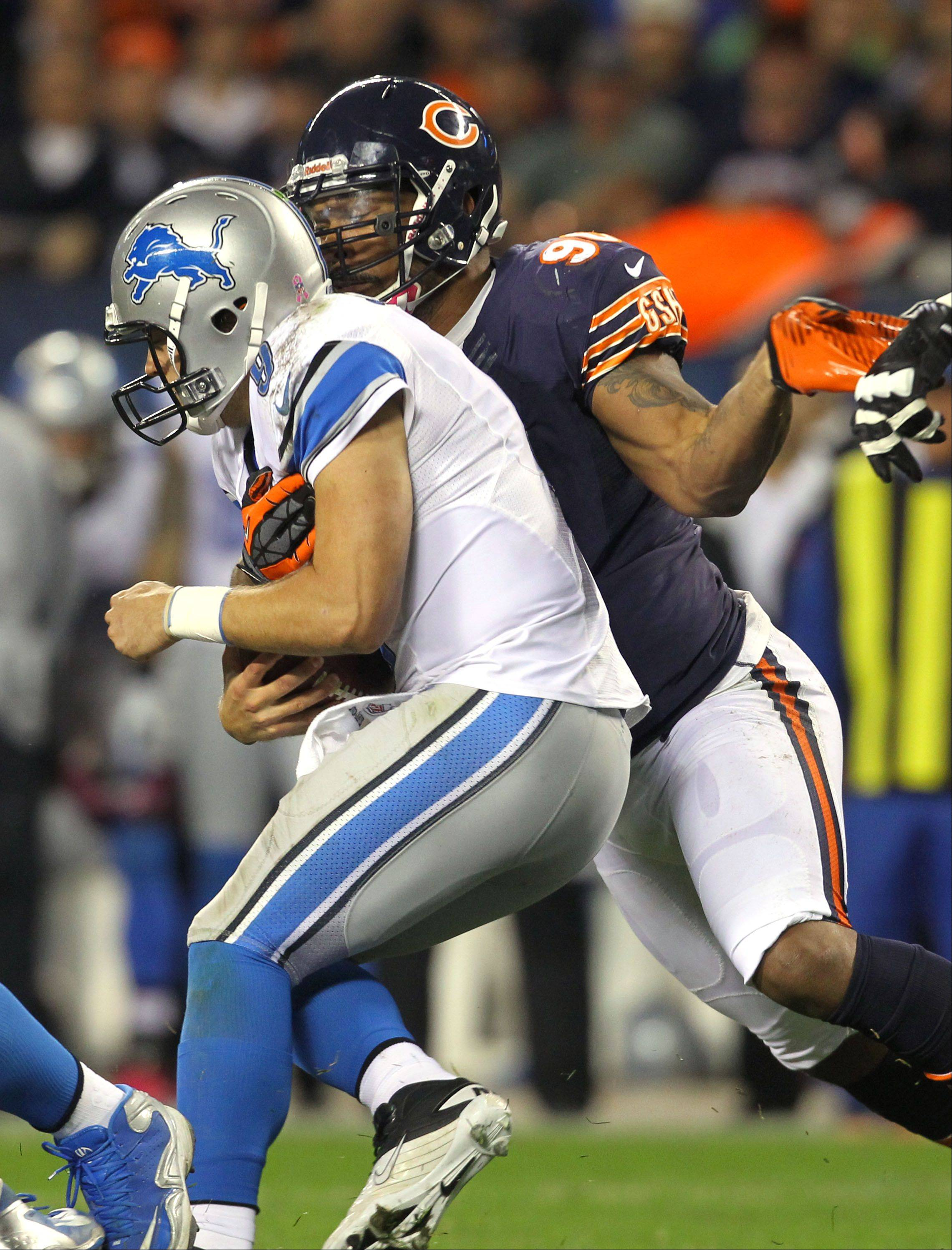 Chicago Bears defensive end Julius Peppers sacks Detroit Lions quarterback Matthew Stafford .