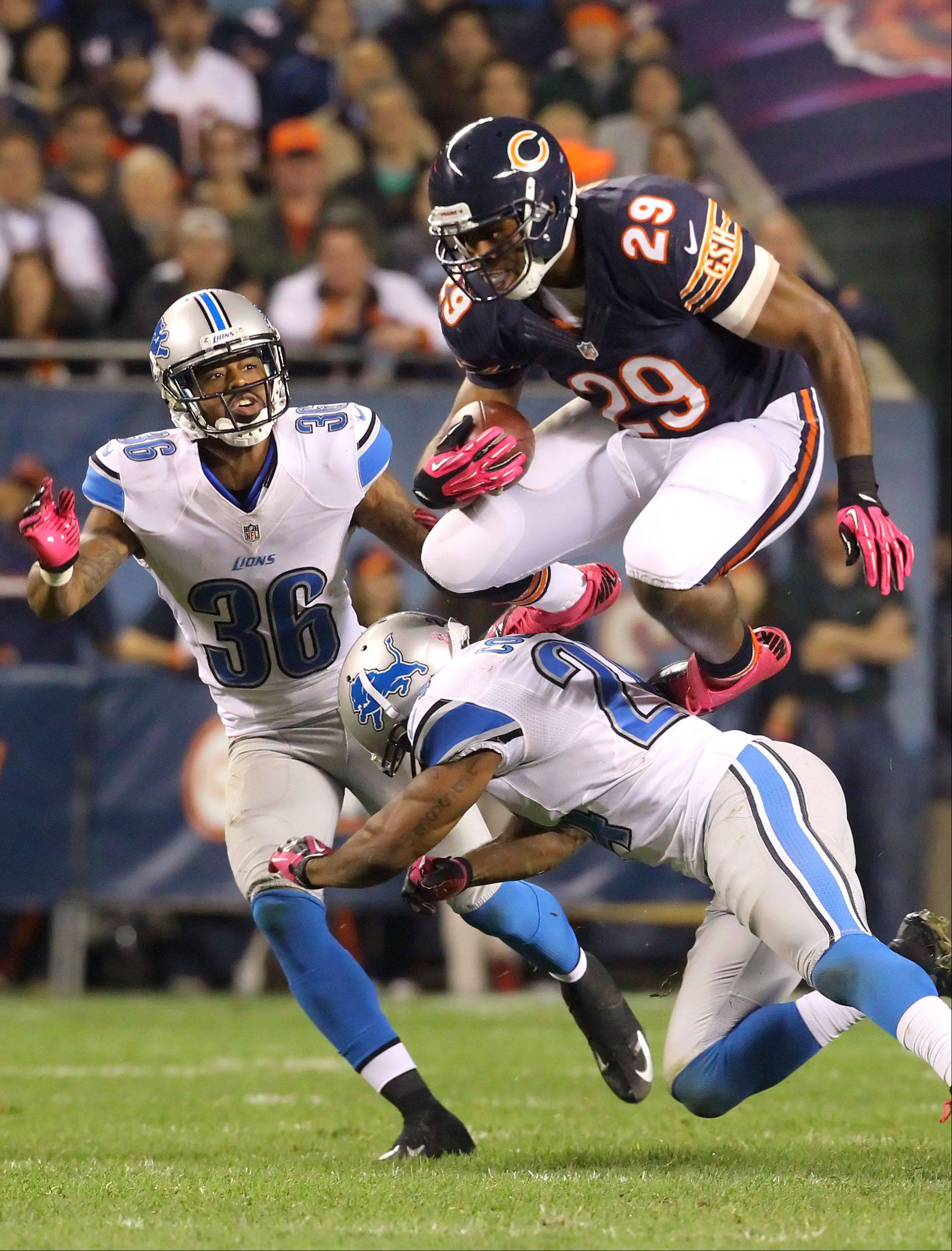 Chicago Bears running back Michael Bush hurdles Detroit Lions strong safety Erik Coleman.