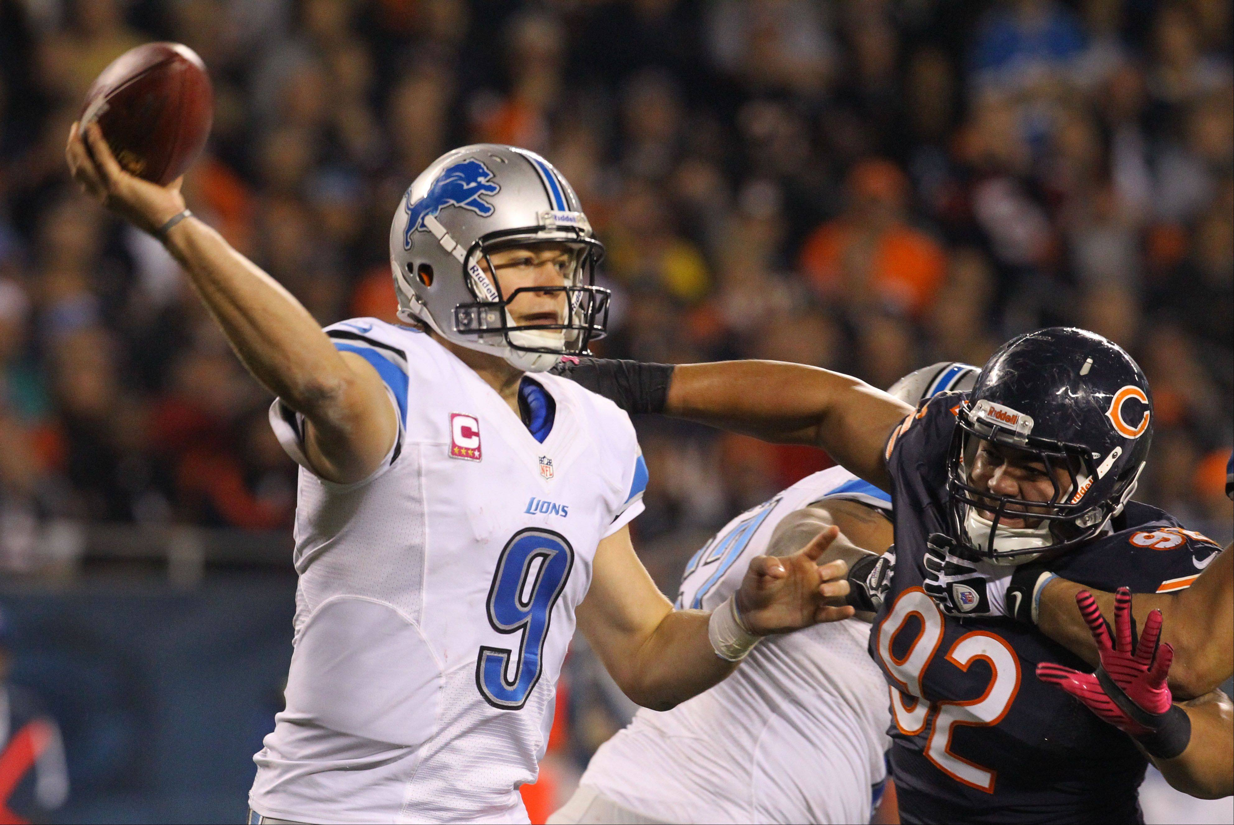 Detroit Lions quarterback Matthew Stafford throws as Chicago Bears defensive tackle Stephen Paea applies pressure.