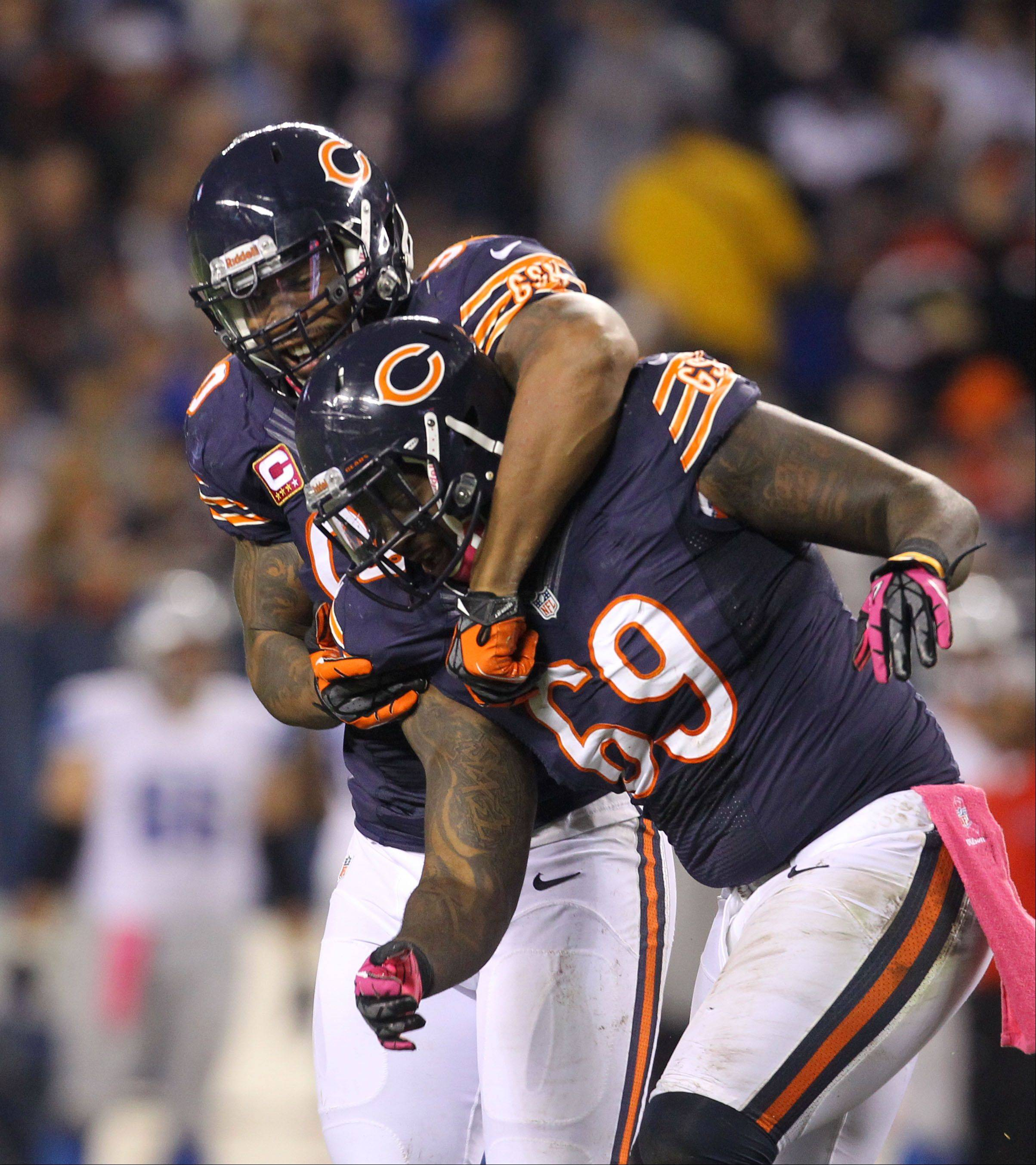 Chicago Bears defensive end Julius Peppers celebrates with Chicago Bears defensive tackle Henry Melton after Peppers sacked Detroit Lions quarterback Matthew Stafford in the first half.