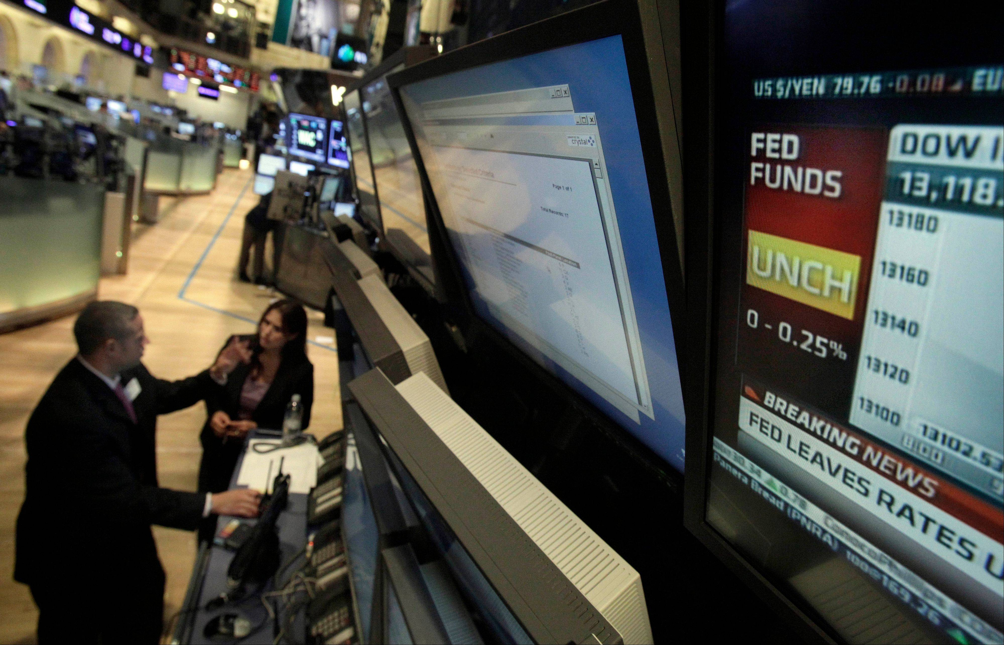 A television screen on the floor of the New York Stock Exchange shows the decision of the Federal Reserve Wednesday. The Fed took no new action after a two-day policy meeting. It wants time to assess whether aggressive steps launched in September will boost growth and job creation.