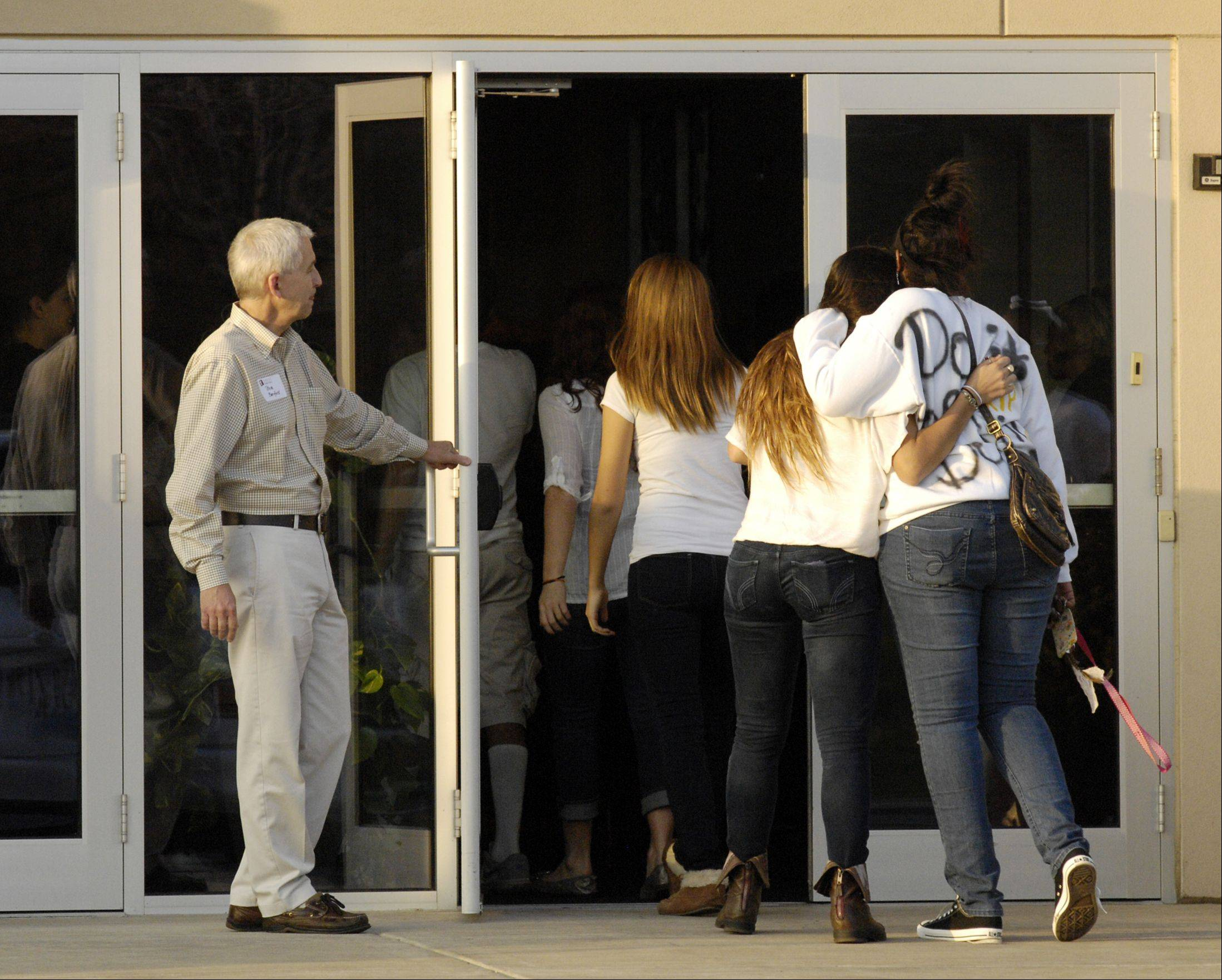 Mourners comfort each other as they enter Faith Lutheran Church in Aurora for a prayer service to remember Devin Meadows, who was killed in an auto accident Tuesday morning.