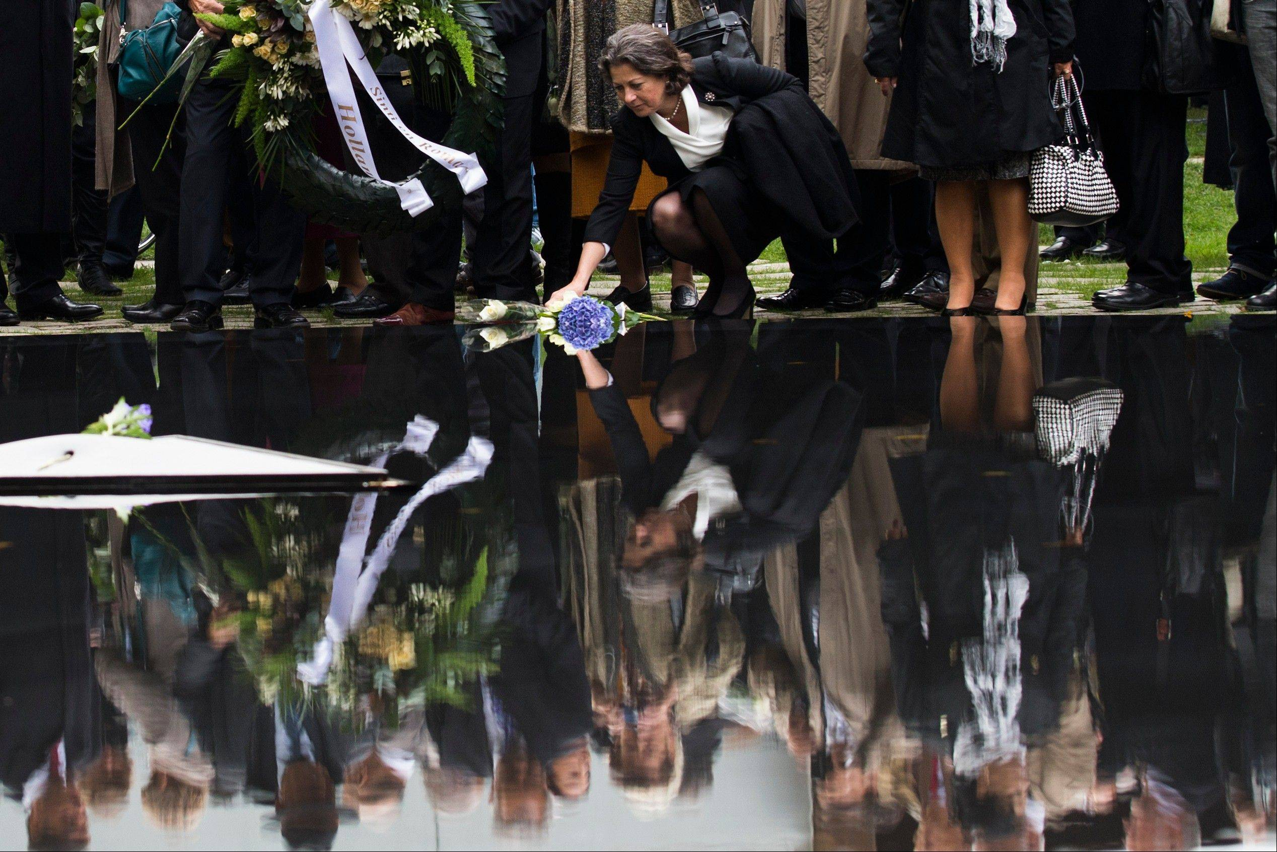 A woman lays down a flower during the inaugural ceremony of the memorial to the murdered European Sinti and Roma who were persecuted as �Gypsies� in Berlin, Wednesday, Oct. 24, 2012. The memorial was designed by artist Dani Karavan consists of a well with a retractable stele with panels carrying information on the persecution and mass murder of this minority under the National Socialist regime.