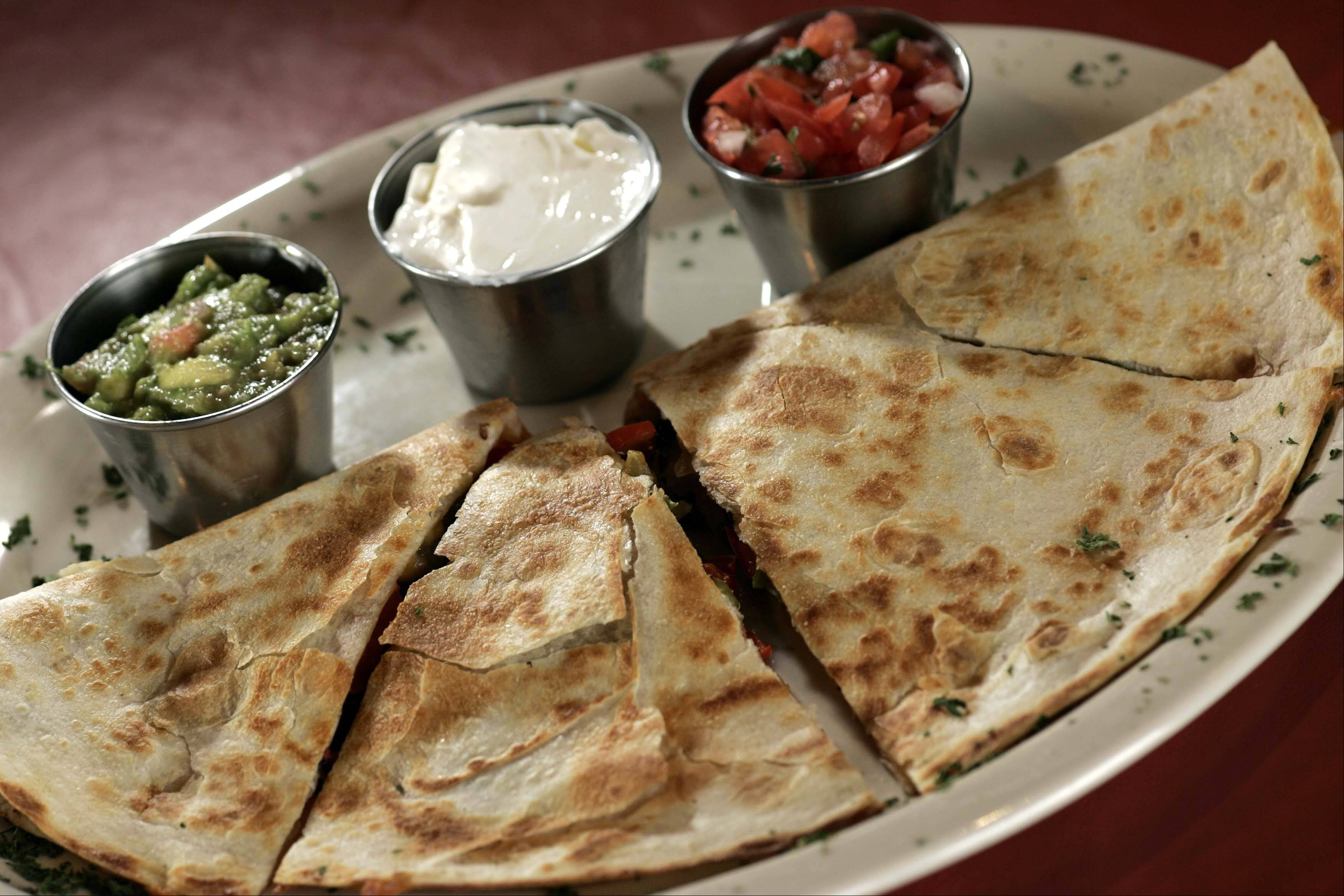 Quesadillas draw extra flavor from sides of guacamole, sour cream and pico de gallo at West End in West Dundee.