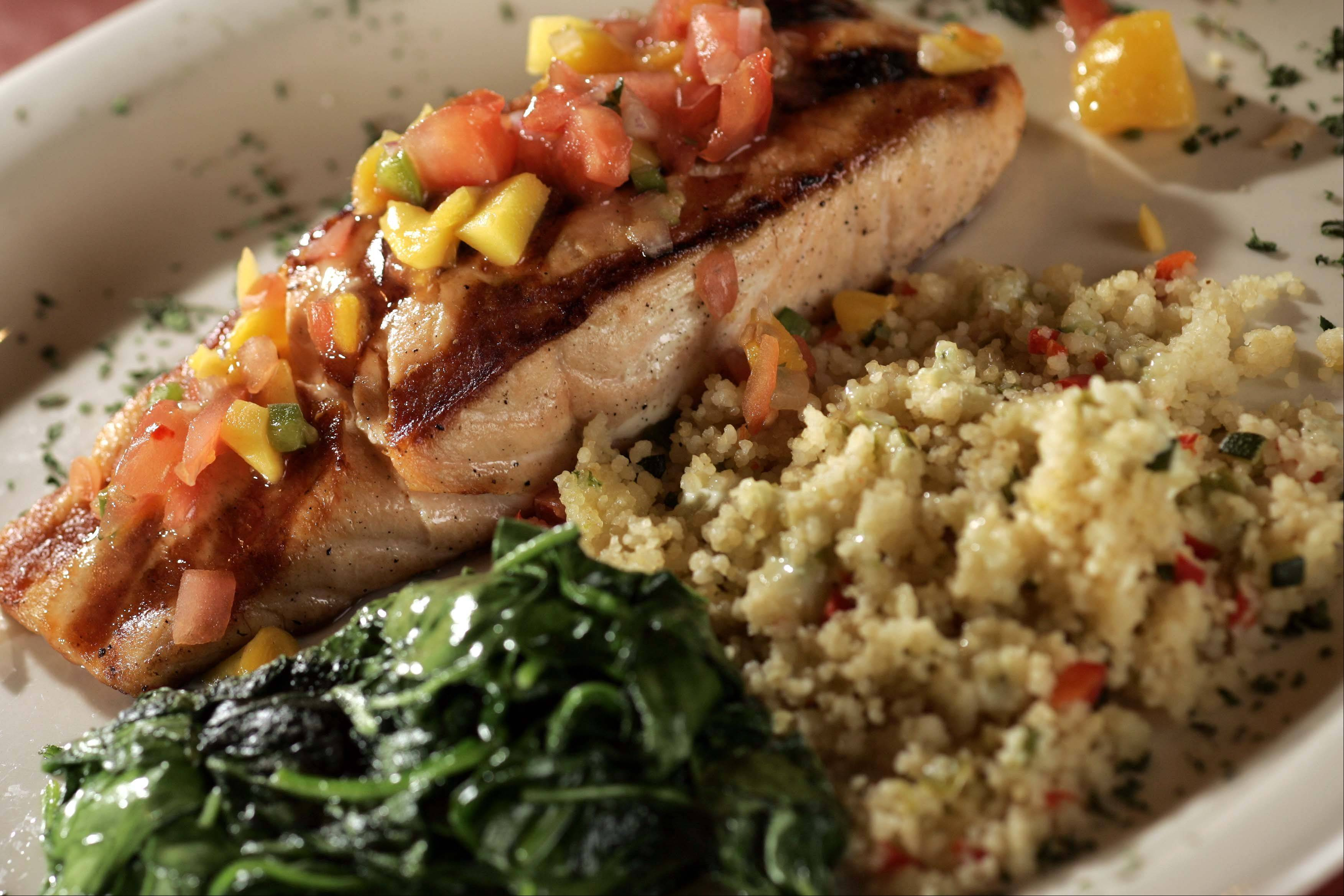 Salmon topped with mango jalape�o salsa comes with well-prepared sides of spinach and quinoa at West End in West Dundee.