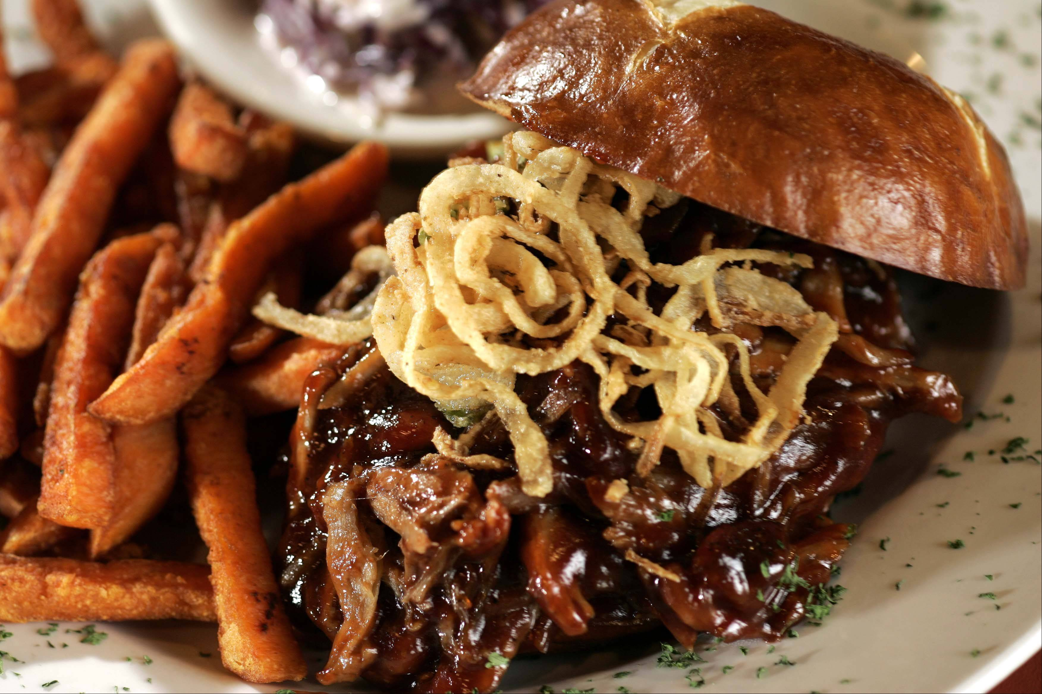 Onion straws top the pulled pork sandwich at West End Restaurant & Bar.