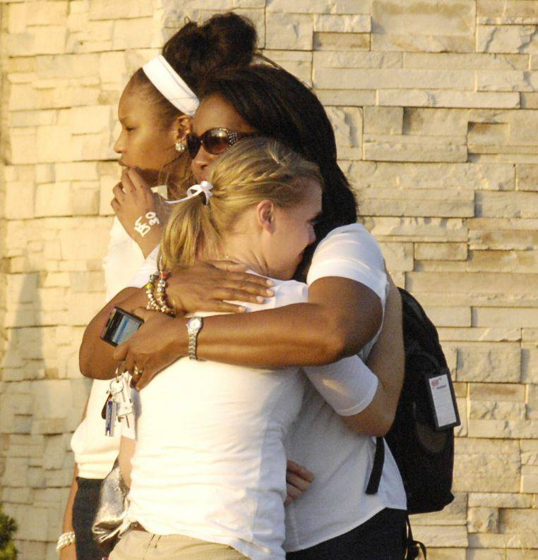 Mourners comfort each other before entering Faith Lutheran Church in Aurora for a prayer service to remember Devin Meadows, who was killed in an auto accident Tuesday morning.