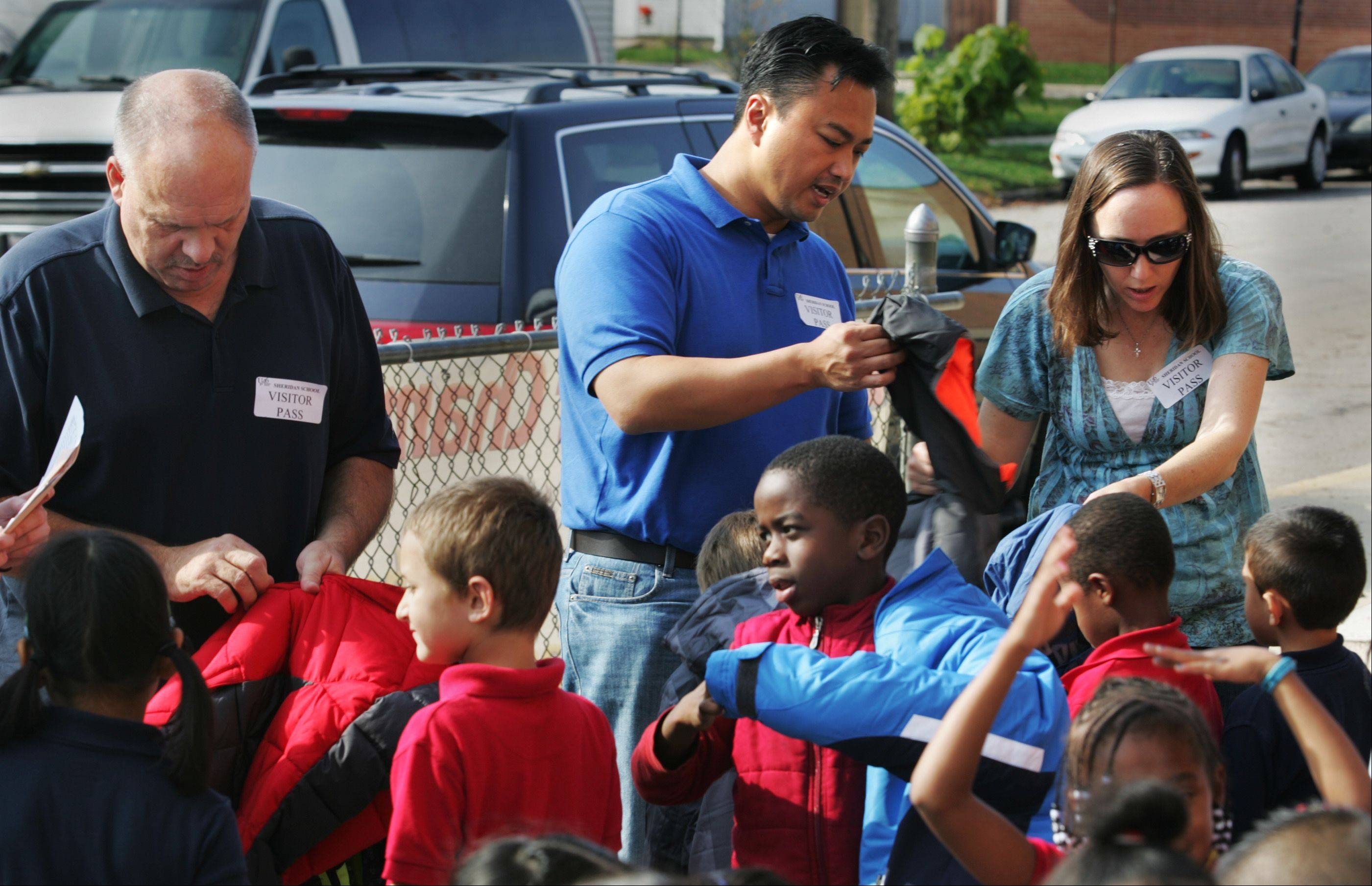 Al and Denise DeGuzman of Hoffman Estates, along with their neighbor Lee Crum, hand out new coats to a group of students at Sheridan Elementary Wednesday in Elgin. The DeGuzmans, of Hoffman Estates, have organized an annual coat drive to help provide winter coats for kids at the school.