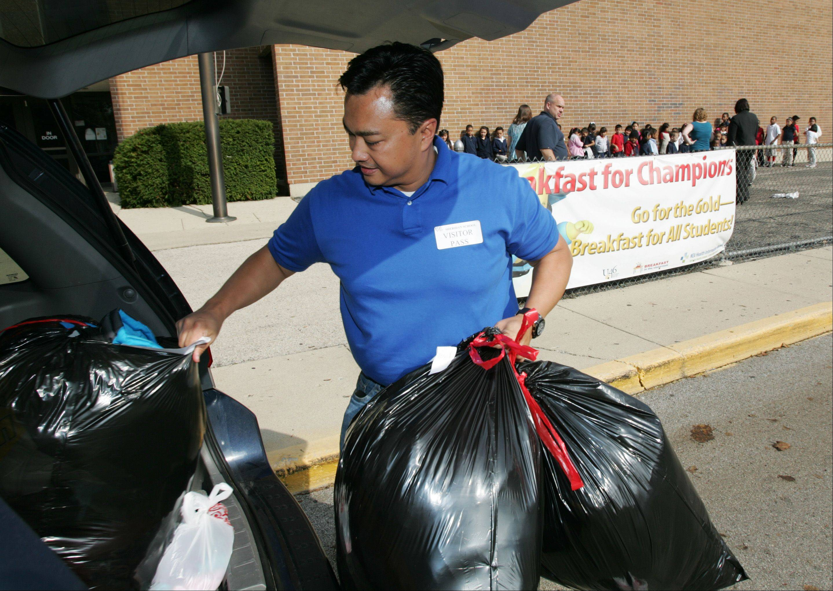 Al DeGuzman hauls out several bags full of new winter coats Wednesday before handing them out to students at Sheridan Elementary in Elgin.