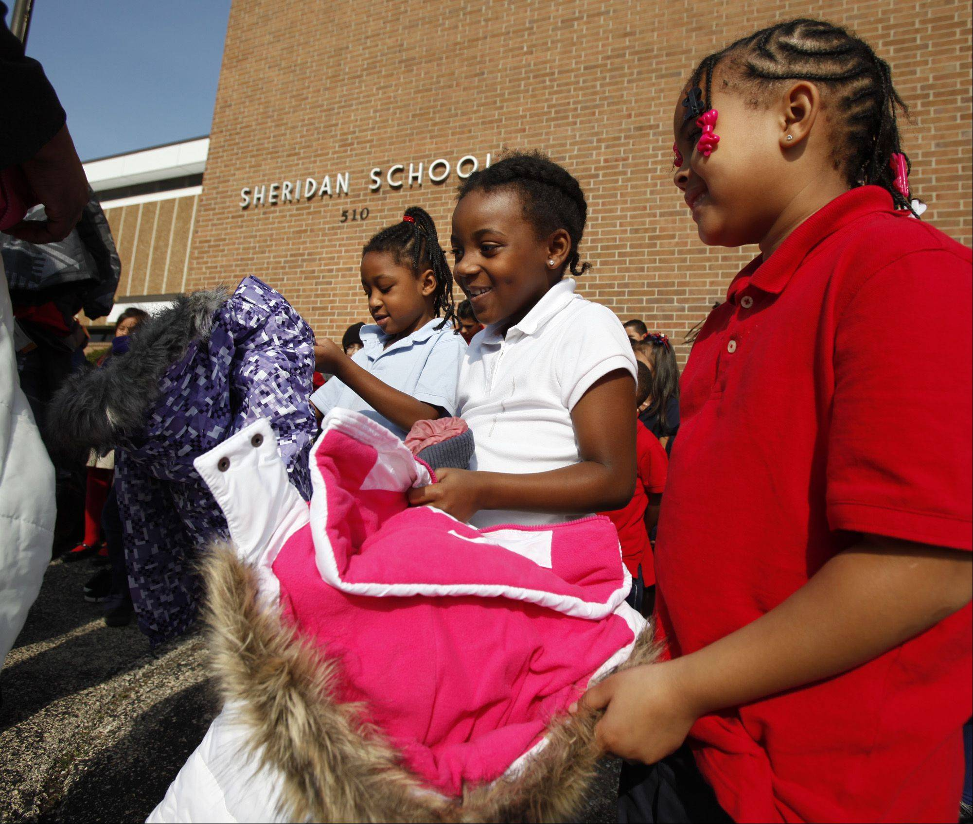 Sheridan Elementary first-graders Taliyah Chandler, left, Chanell Walker and Tamya Clay check out their new winter coats outside the school Wednesday in Elgin.
