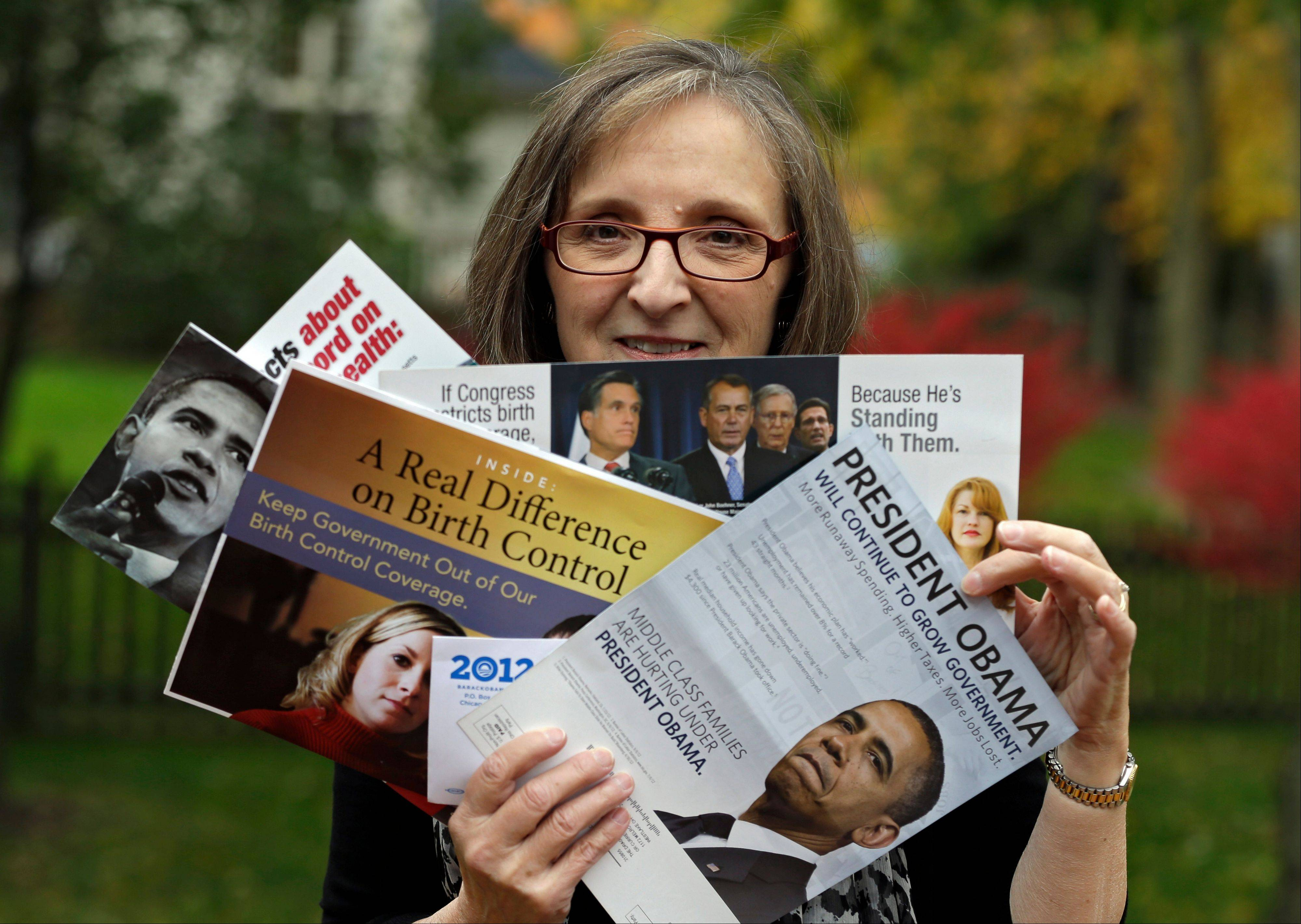 Jean Gianfagna displays some of the political mailers her family receives at her home in Westlake, Ohio. Television commercials may be king, but millions of dollars a week are fueling mail ads that are burying swing-state voters in appeals from the presidential candidates, political parties and their allied groups.