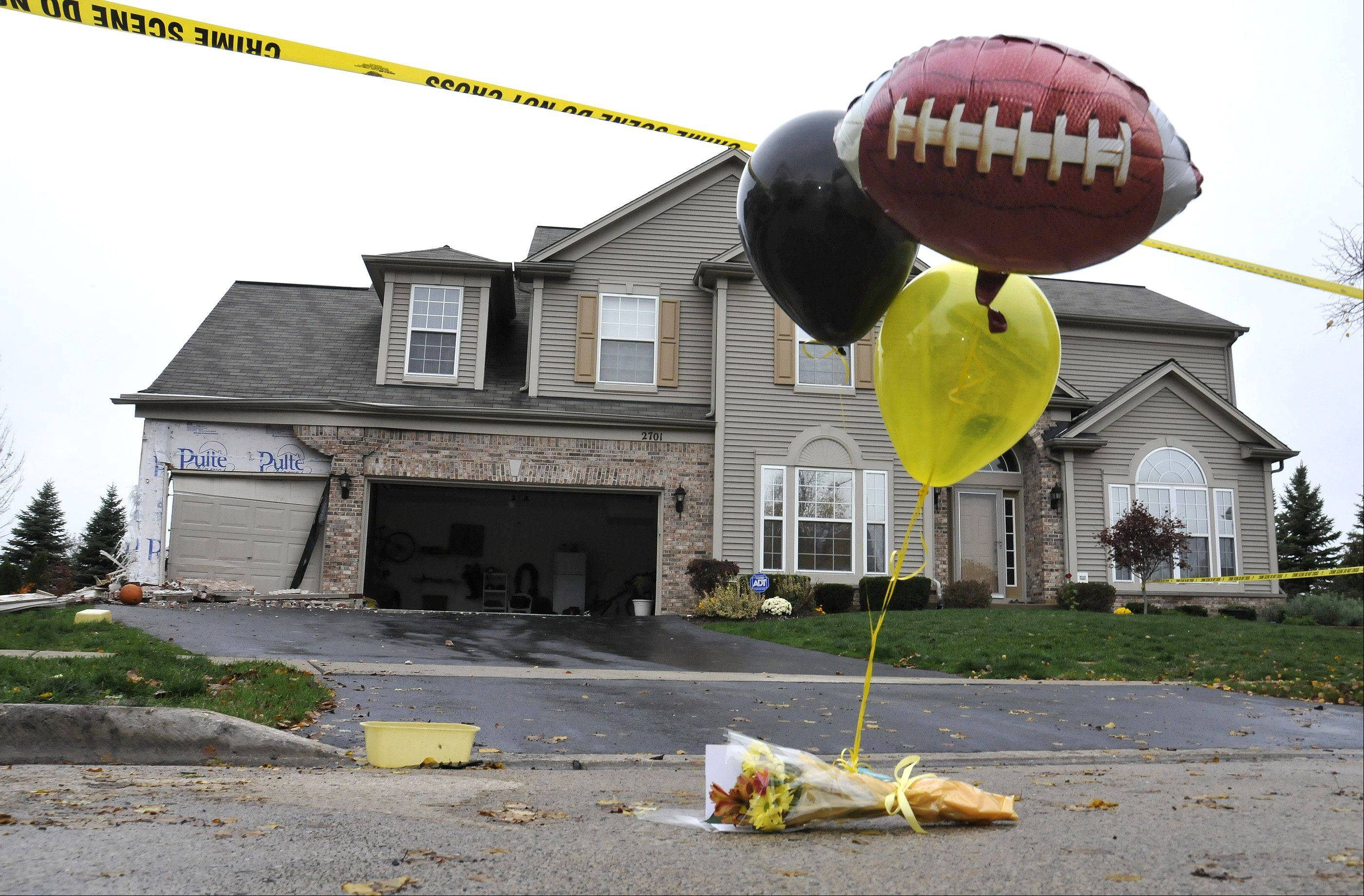 Friends and students of Metea Valley High School football player and fellow student Devin Meadows stop by the house on the 2700 block of Hamman Way in Aurora Tuesday morning. Meadows was killed earlier this morning when a car he was riding in went out of control and smashed into the house.