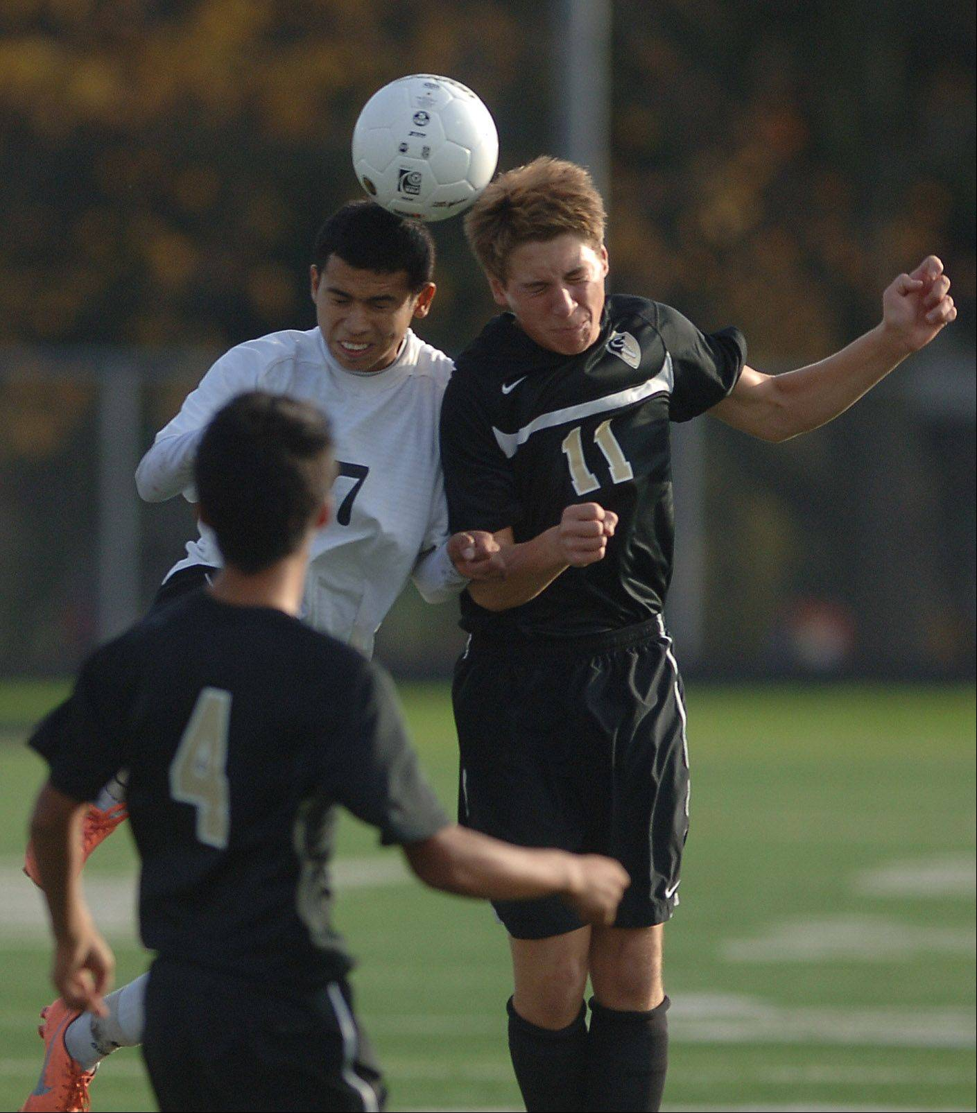 Harvard's Christian Carrillo and Grayslake North's Colin Grever (11) compete for the header during the Class 2A soccer sectional semifinal game Wednesday at Grayslake Central.