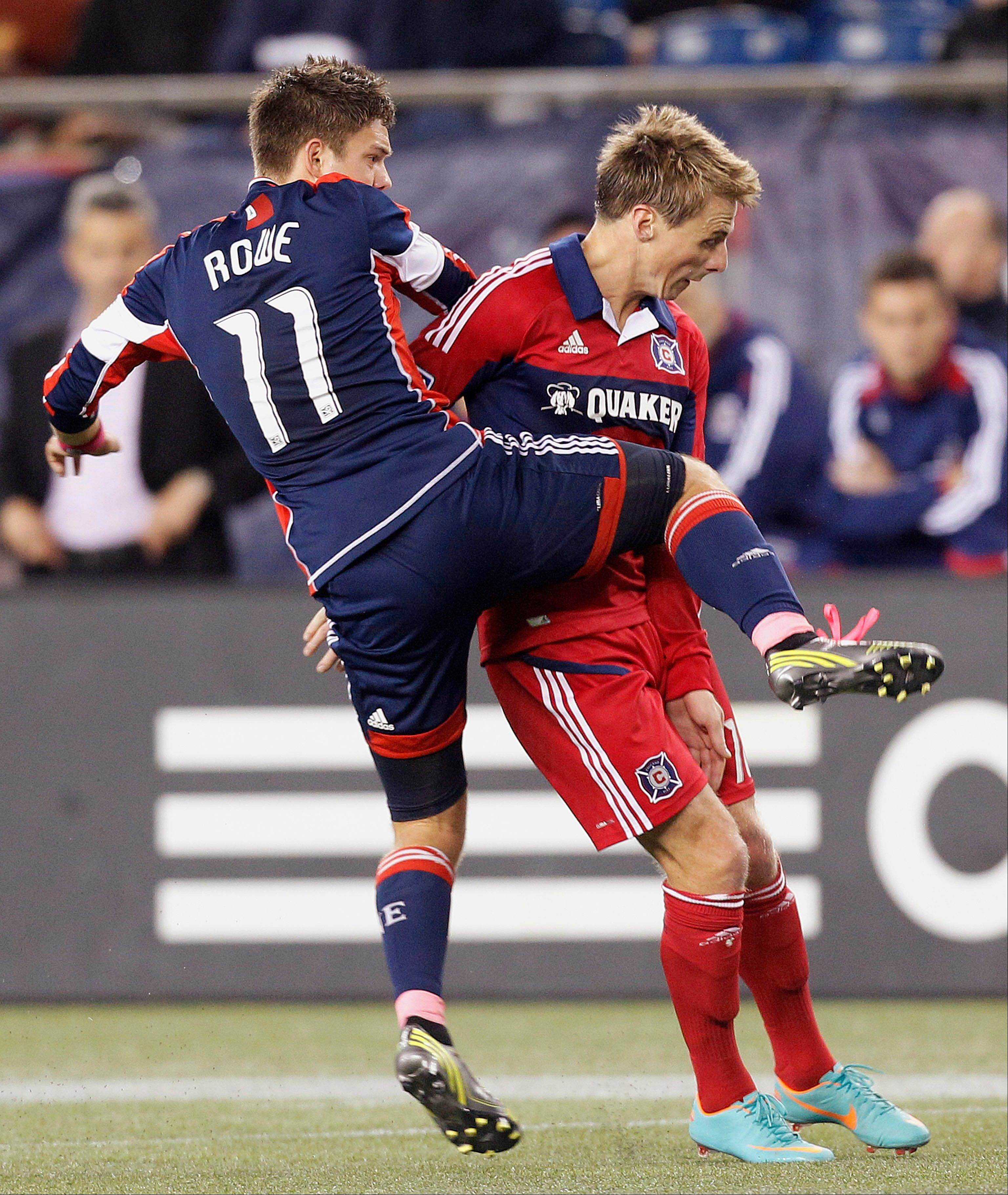 New England Revolution midfielder Kelyn Rowe (11) knees Chicago Fire forward Chris Rolfe during their MLS match in Foxborough, Mass., Saturday. The Revolution won 1-0.
