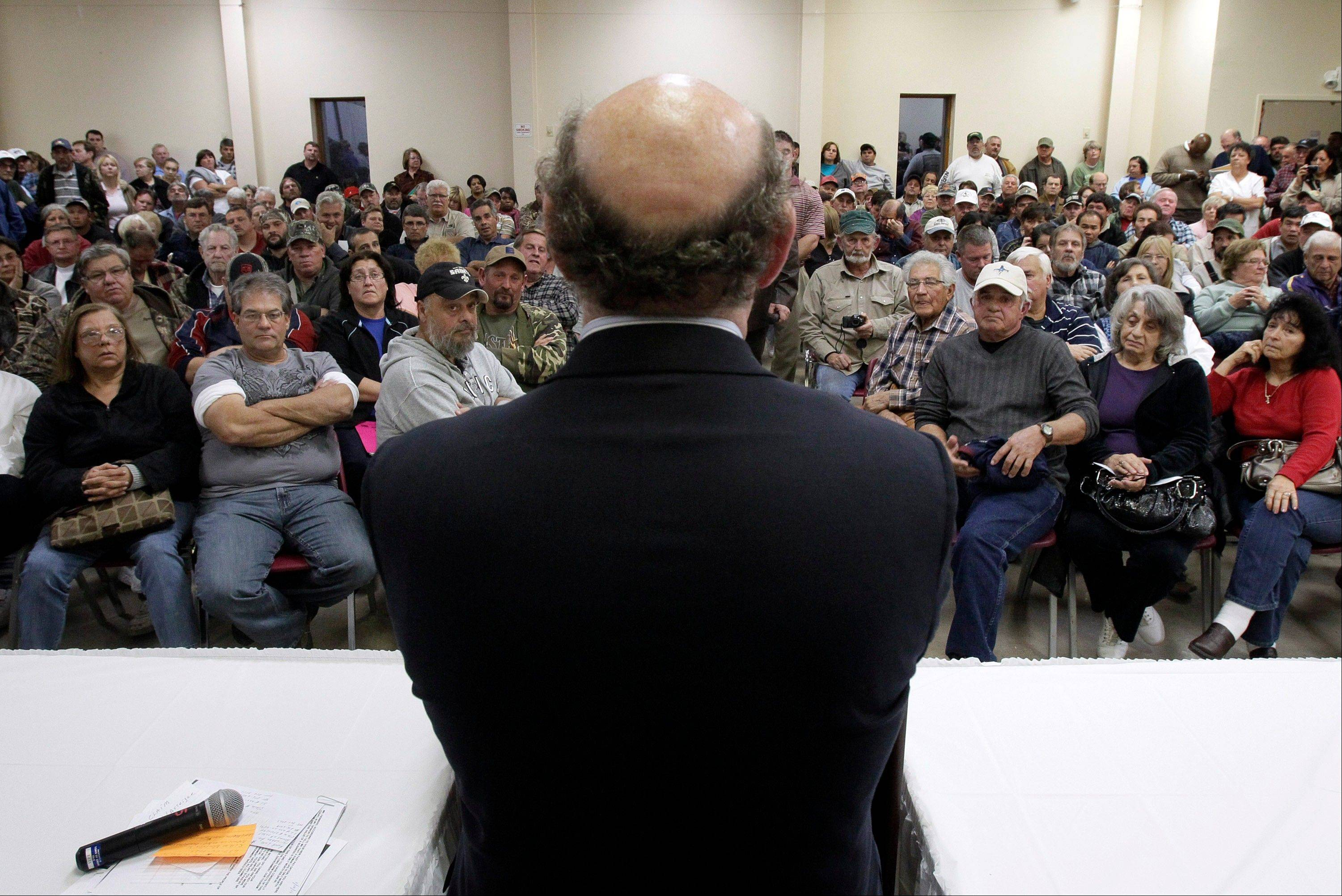 In this Jan. 10, 2011, photo, claimants listen to BP oil spill fund administrator Kenneth Feinberg, center, as he speaks at a town hall meeting in Grand Isle, La. In court filings Monday, the oil giant BP asked a federal judge to disregard objections from a fraction of claimants and give final approval to a proposed multibillion-dollar settlement for economic damages from the Gulf spill.