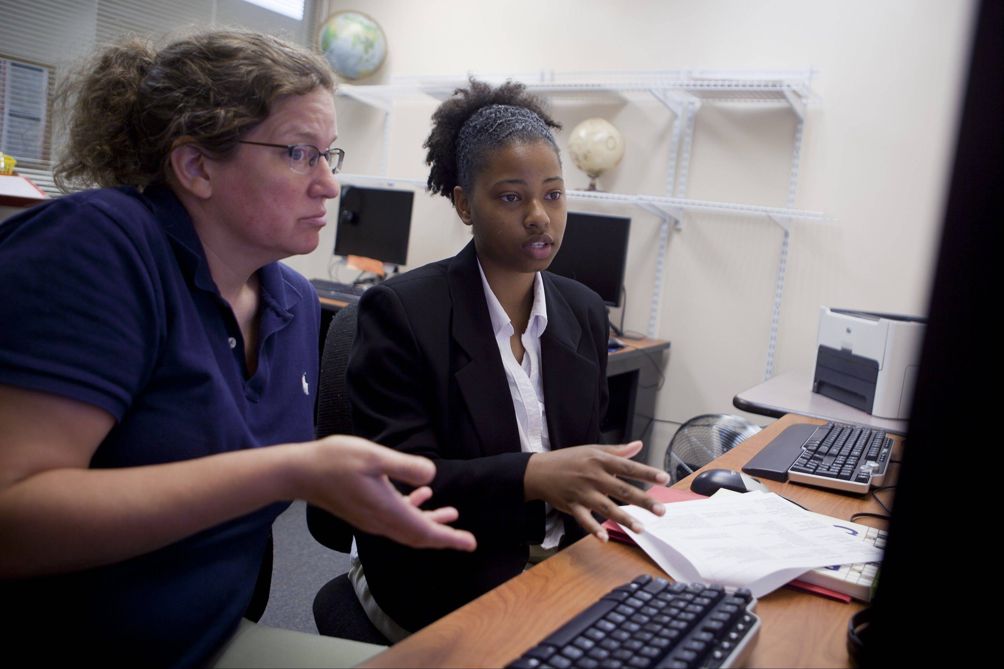 Heidi Gauthier, left, helps jobseeker Jennifer Thomas look at job postings online at the education and employment area of N Street Village community center in Washington, D.C..