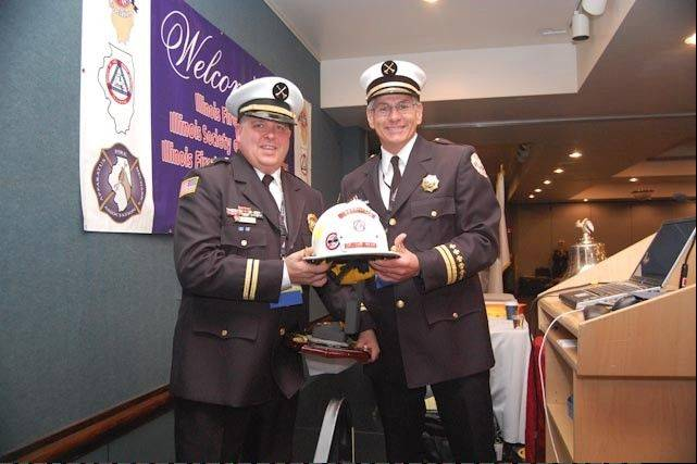Bloomingdale Battalion Chief Jeff Janus, left, receives the Instructor of the Year helmet from the Illinois Society of Fire Service Instructors. The helmet was presented by Forest Reeder, Des Plaines Fire Department�s chief of training and safety and last year�s winner.