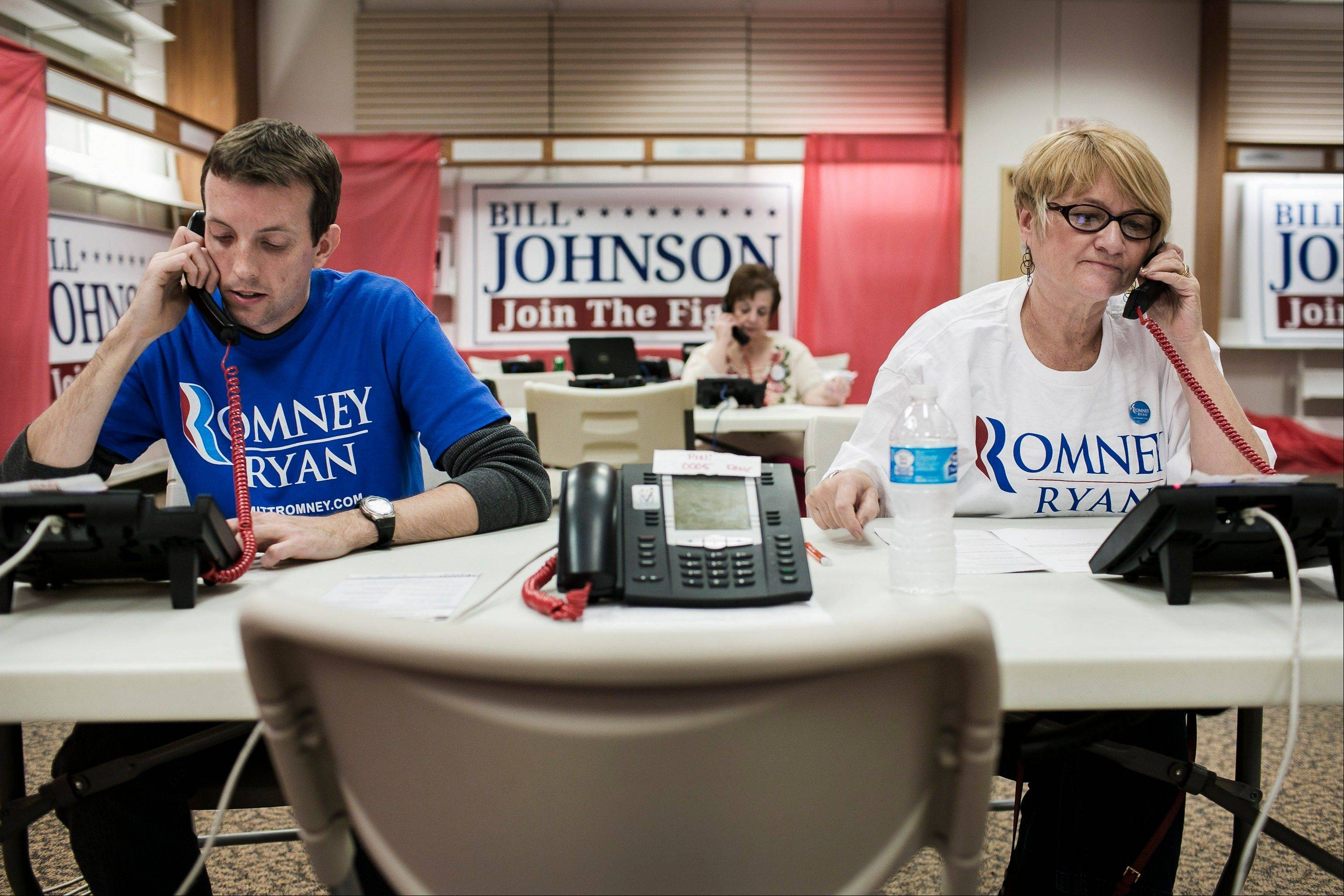 Volunteers Susan Conaway, right, of Toronto, Ohio, and Ryan Call, of Steubenville, Ohio, make phone calls at Republican presidential candidate Mitt Romney�s campaign office in Steubenville, Ohio, U.S., on Wednesday, Oct. 24, 2012.