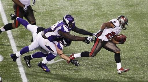 Tampa Bay Buccaneers running back Doug Martin (22) breaks a tackle by Minnesota Vikings defensive tackle Letroy Guion (98) during a 64-yard touchdown reception in the second half of an NFL football game Thursday.