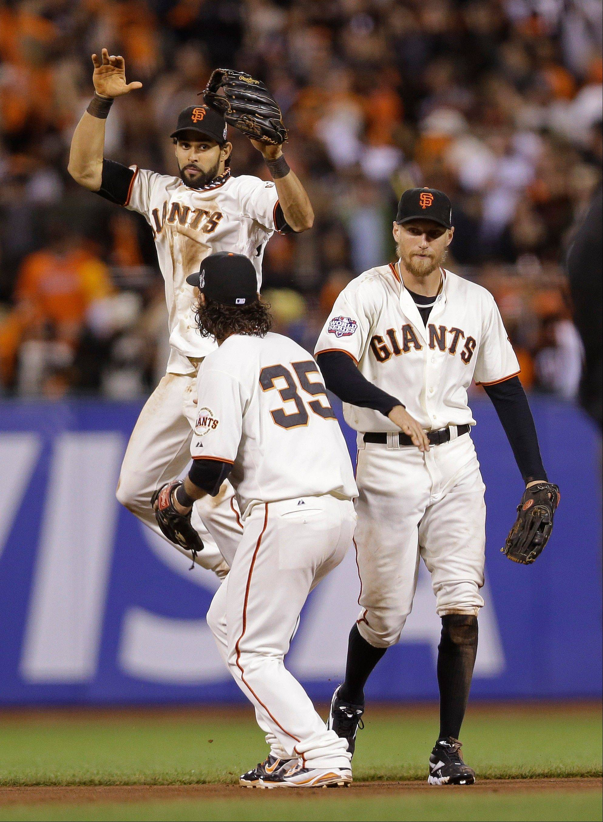 San Francisco Giants' Angel Pagan, Brandon Crawford (35) and Hunter Pence, right, celebrate after the Giants defeated the Detroit Tigers, 2-0, in Game 2 of baseball's World Series Thursday, Oct. 25, 2012, in San Francisco. (AP Photo/Marcio Jose Sanchez)
