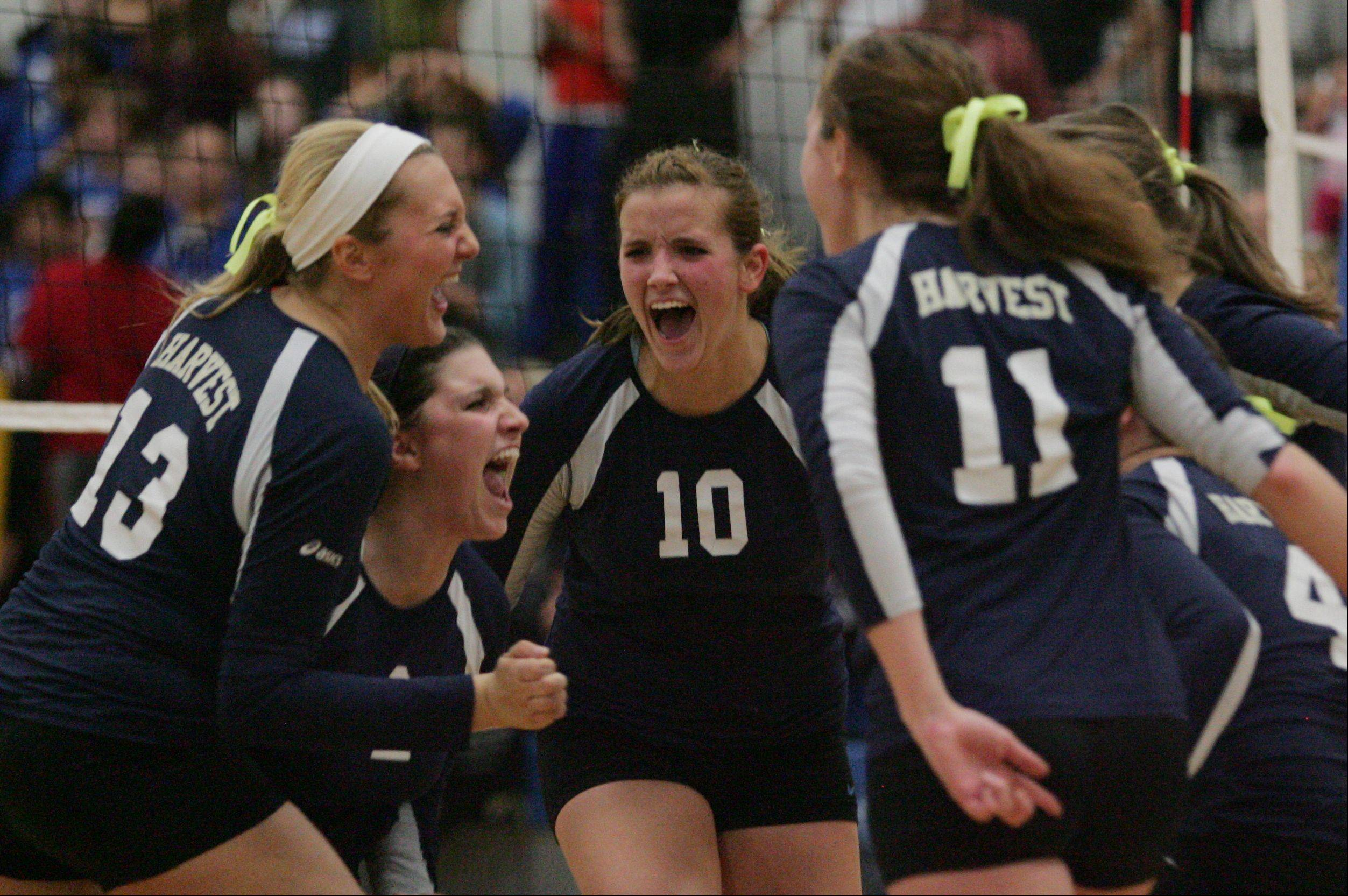Harvest Christian volleyball players Erica Manusos, left, Jordan Sollars, Sydney Doby and Chloe Corbett celebrate their match-winning point Thursday night against Westminster Christian in the Class 1A regional final at Westminster.