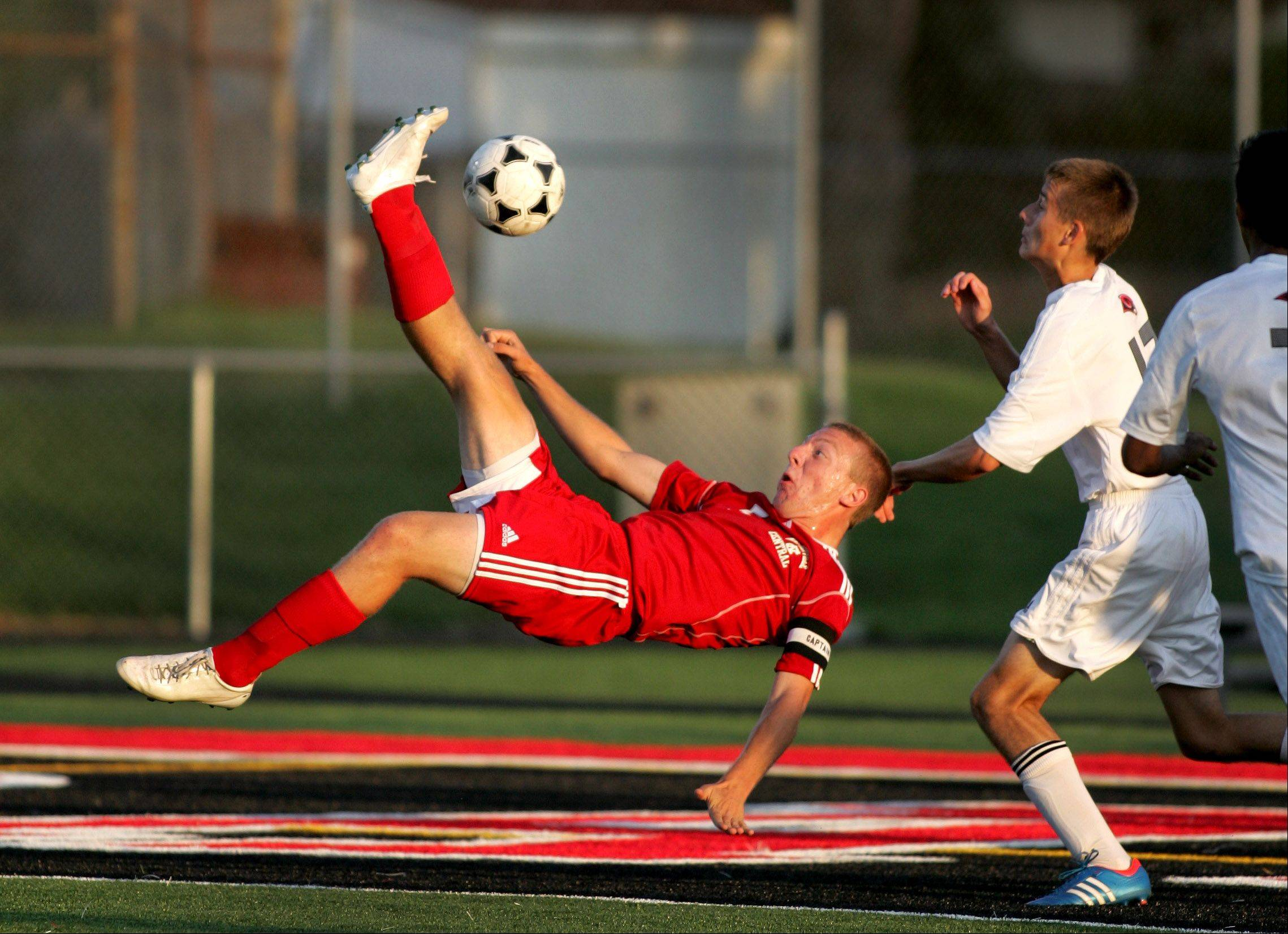 Pat Flynn of Naperville Central attempts to kick it back for a goal over Ivailo Alexandrov of Glenbard East, right, in boys soccer action Tuesday in Lombard.