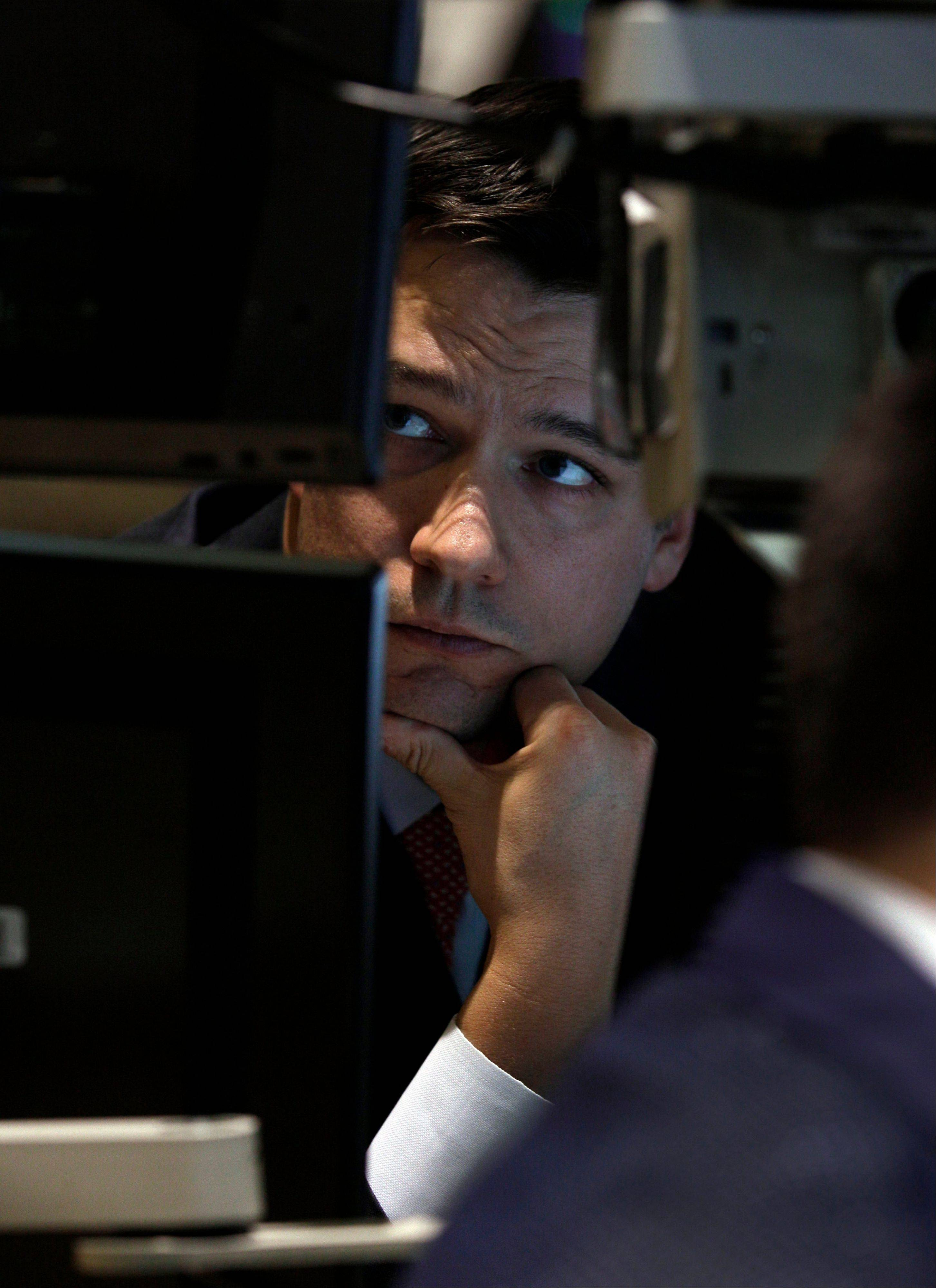 Specialist Robert Canzani is framed by his monitors as he works on the floor of the New York Stock Exchange Wednesday.