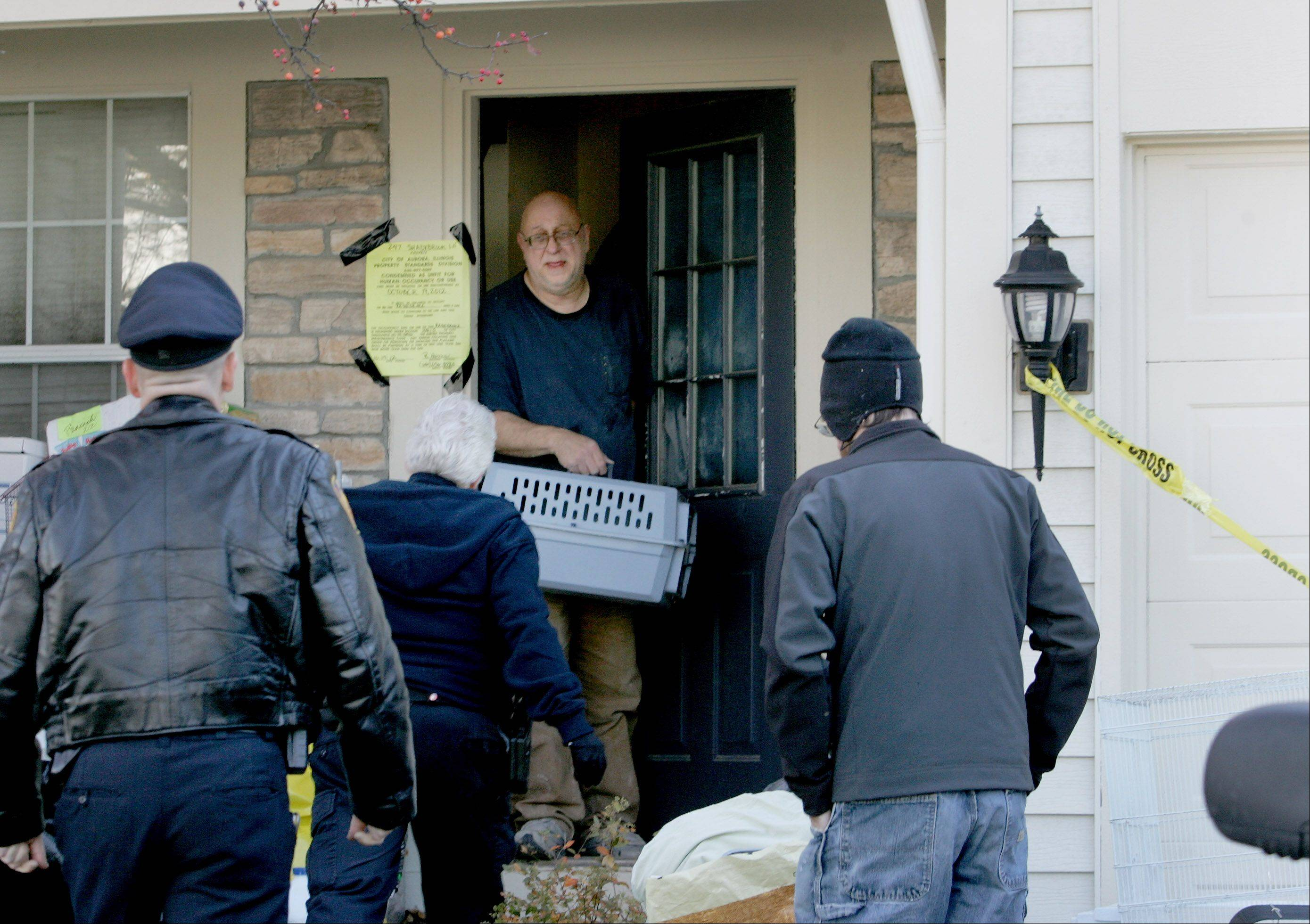 Homeowner Dave Skeberdis brings out a caged bird to give to the Greater Chicago Chicago Cage Bird Club before the city of Aurora took over the cleanup of his house on Friday.
