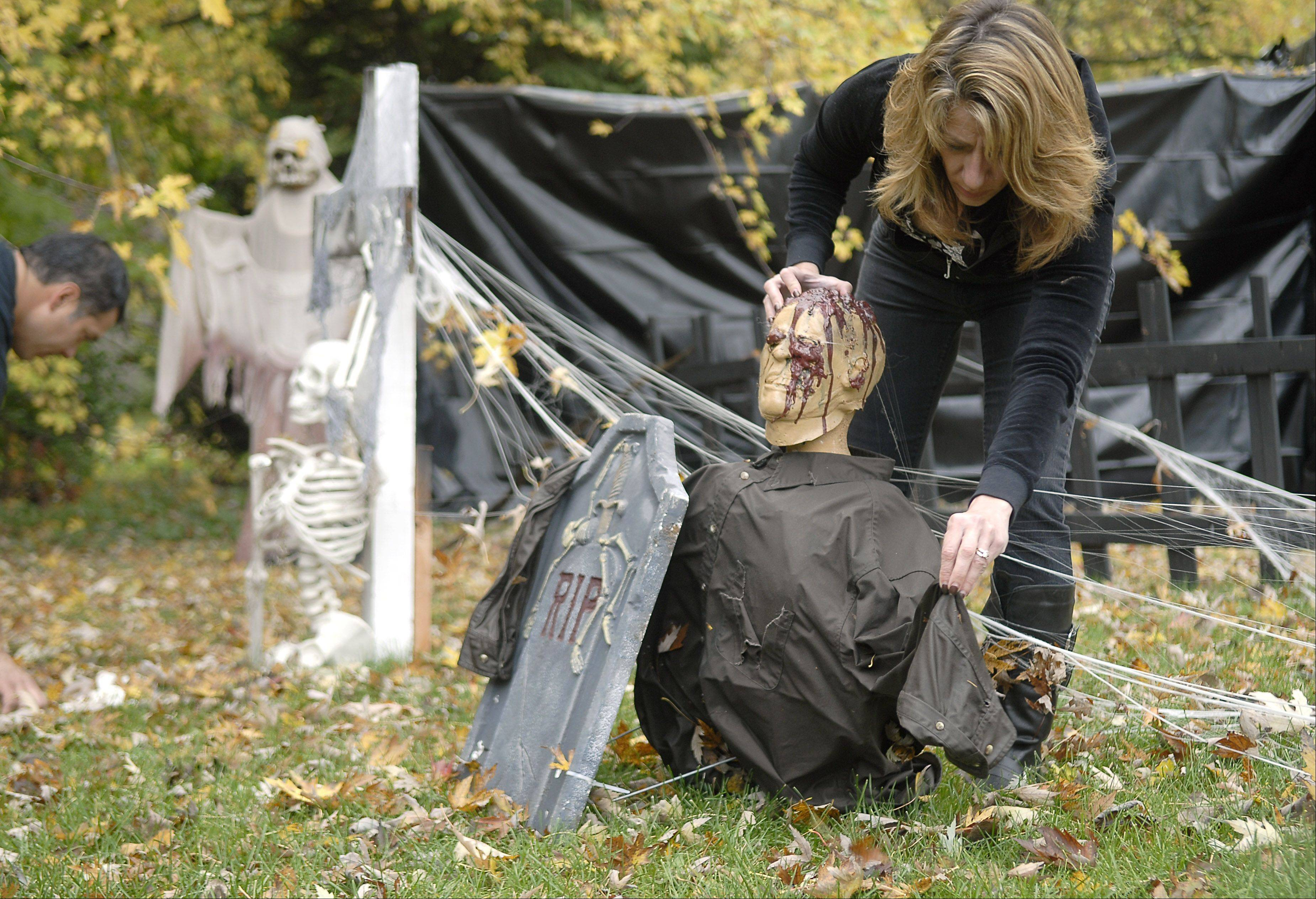 Christine Acosta straightens out a body in their backyard graveyard while husband Cesilio adjusts a skeleton.