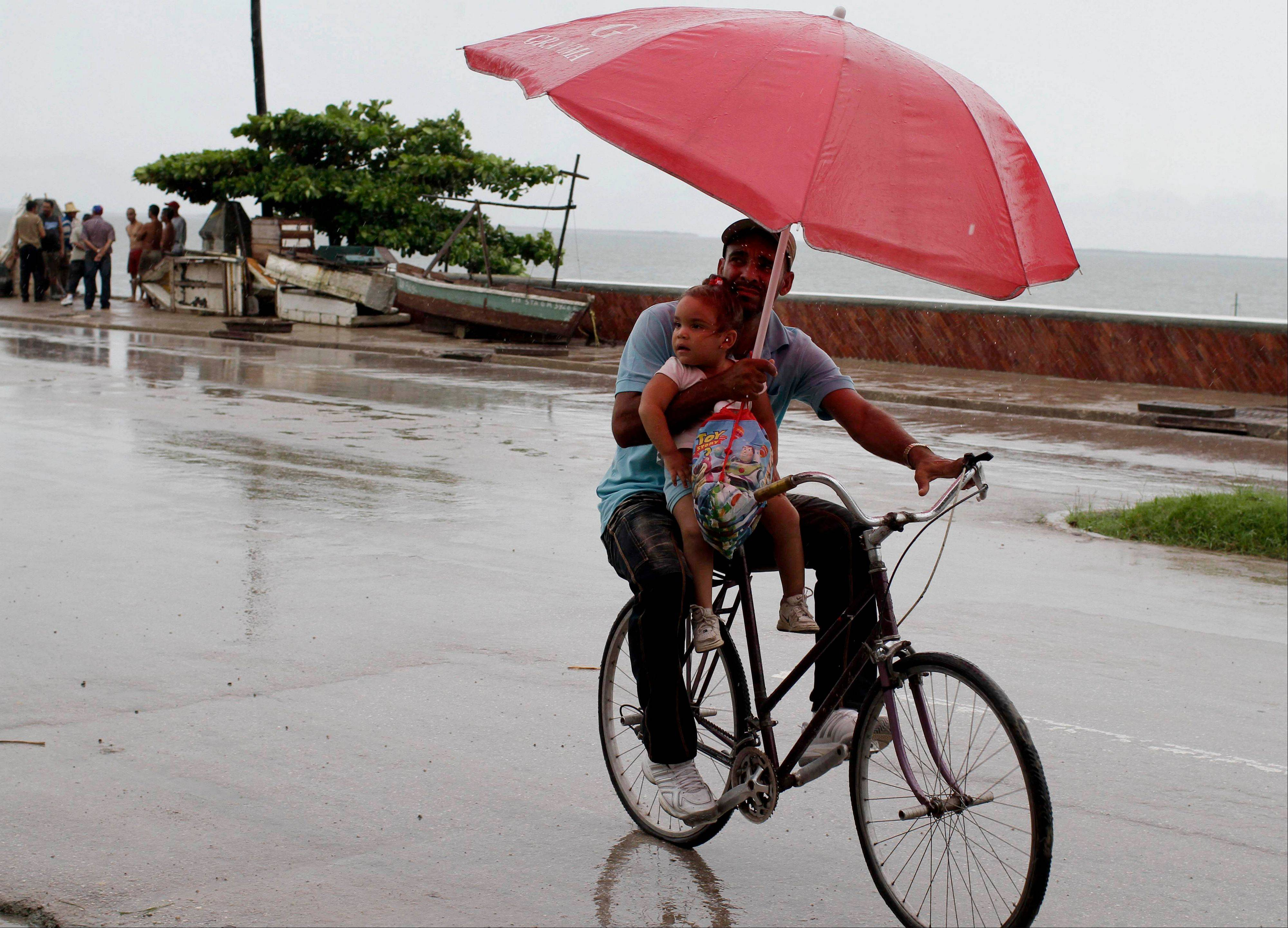 A man balances a child and umbrella on his bike as it rains during the approach of Hurricane Sandy in Manzanillo, Cuba, Wednesday.