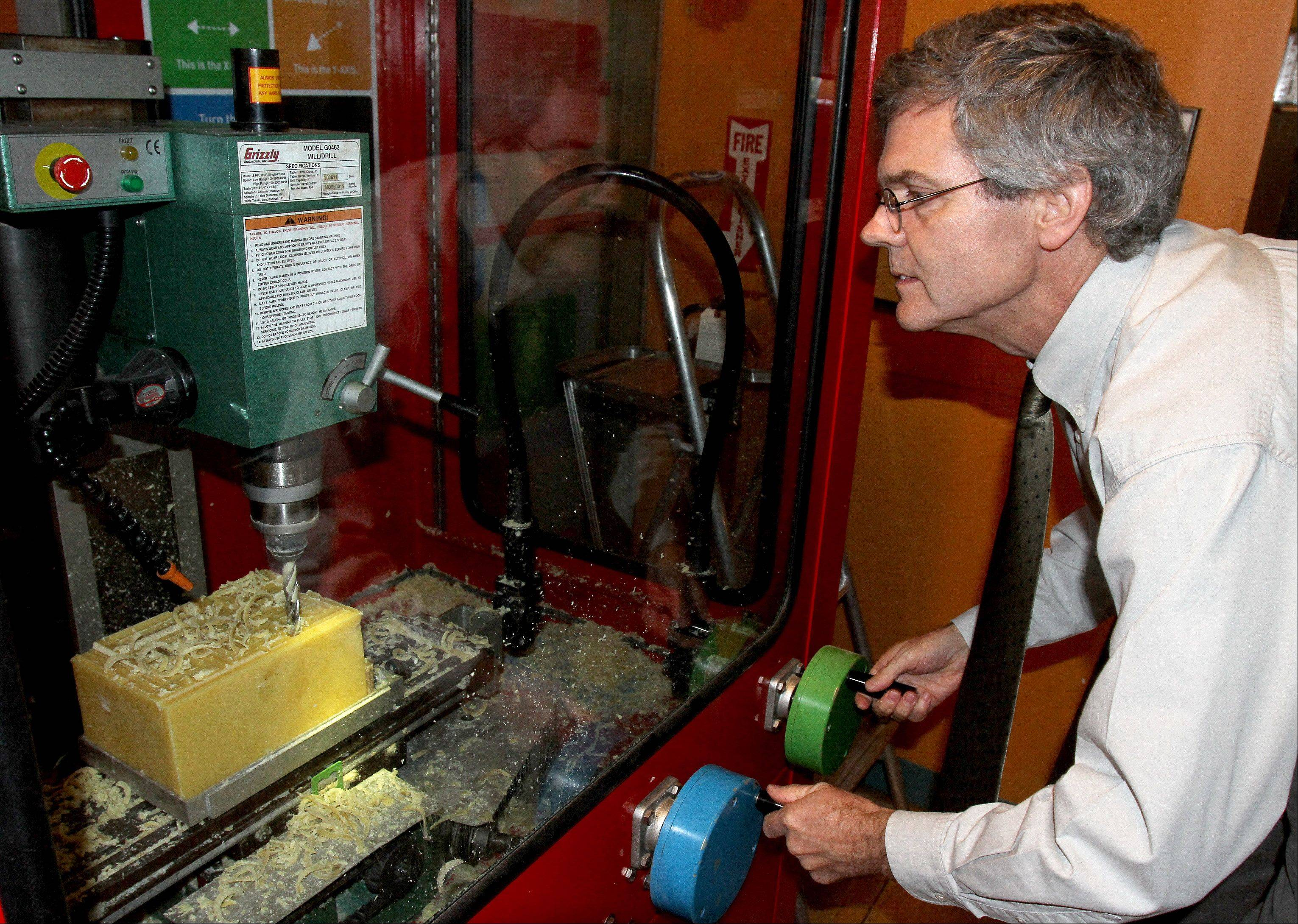 Peter Crabb, director of exhibits, demonstrates a 3-Axis Mill, one of the displays in How People Make Things, visiting through January at the DuPage Children's Museum.