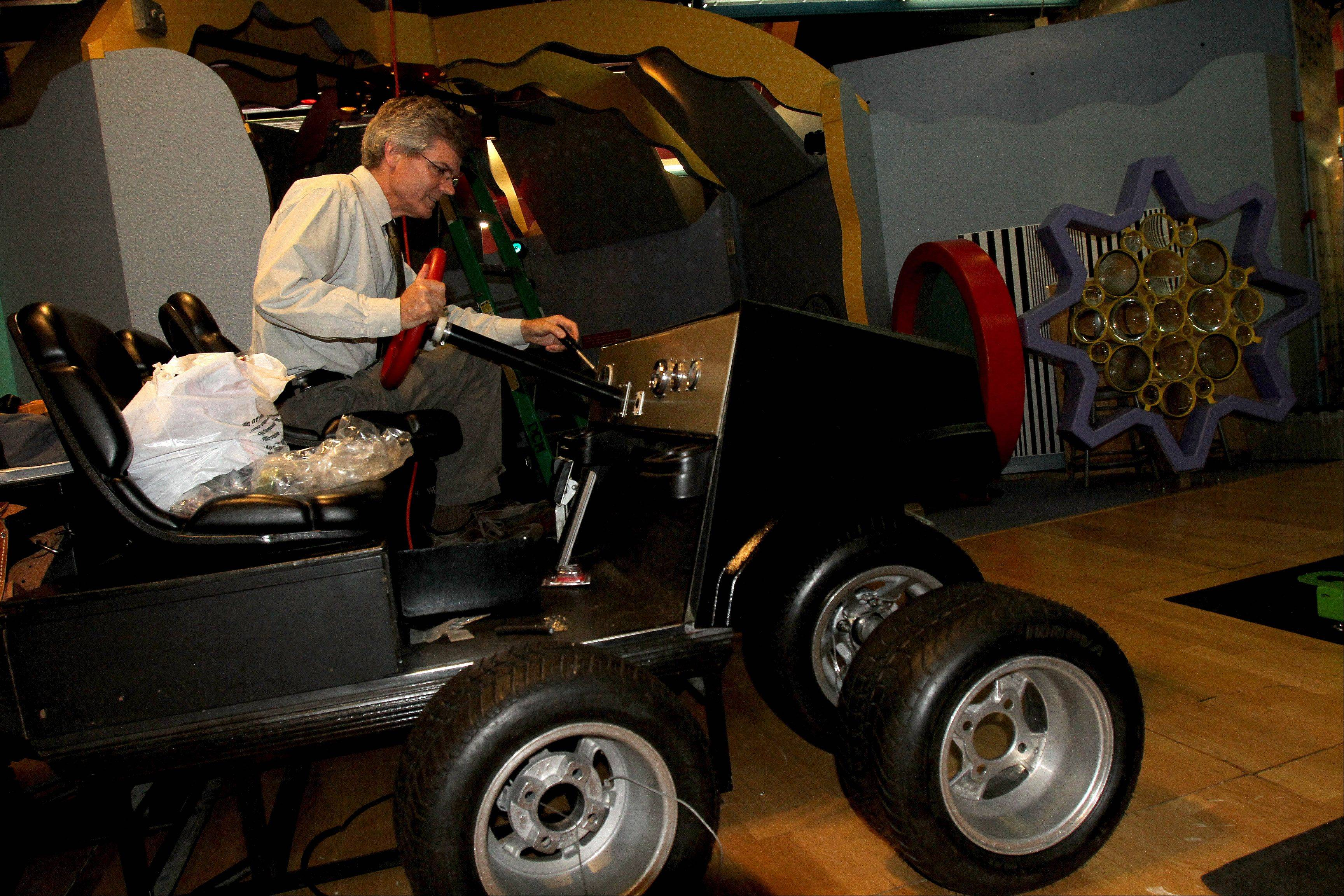 The How People Make Things exhibit invites visitors to get up close with mechanics and production processes. Here, Peter Crabb, director of exhibits, checks out a golf cart on which kids will be able to exchange steering wheels.