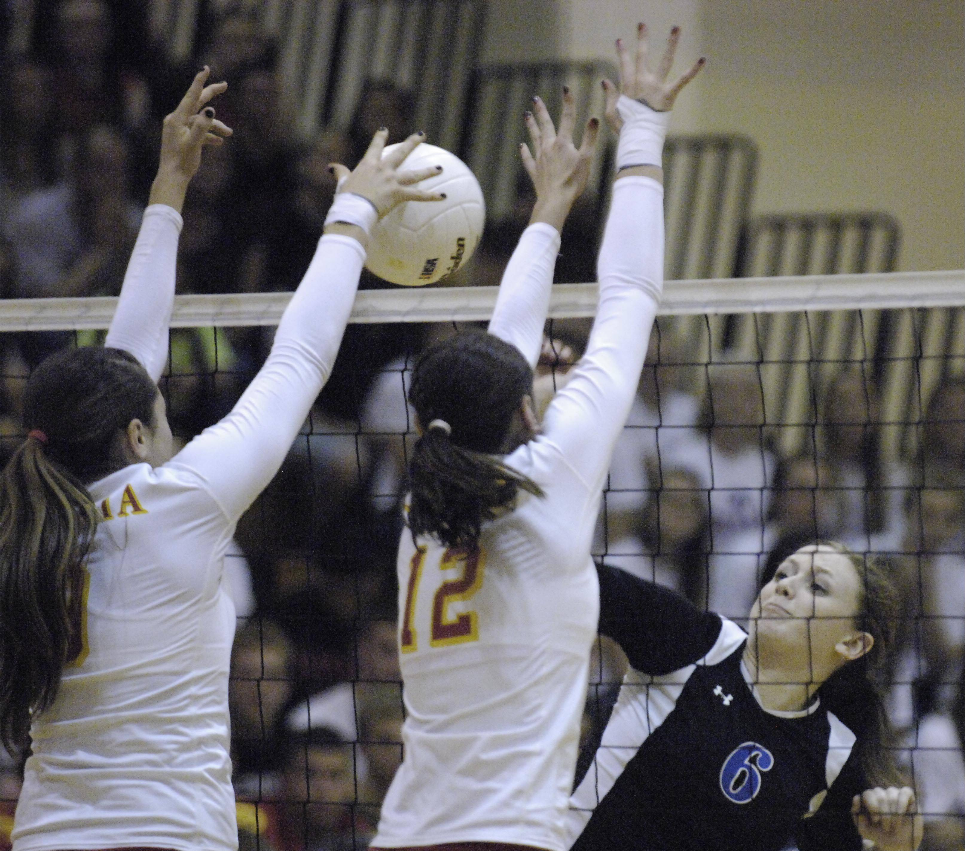 Batavia's Heather Meyer and Shea Thayer stop a shot by Geneva's Renner Burns Thursday in the regional championship.